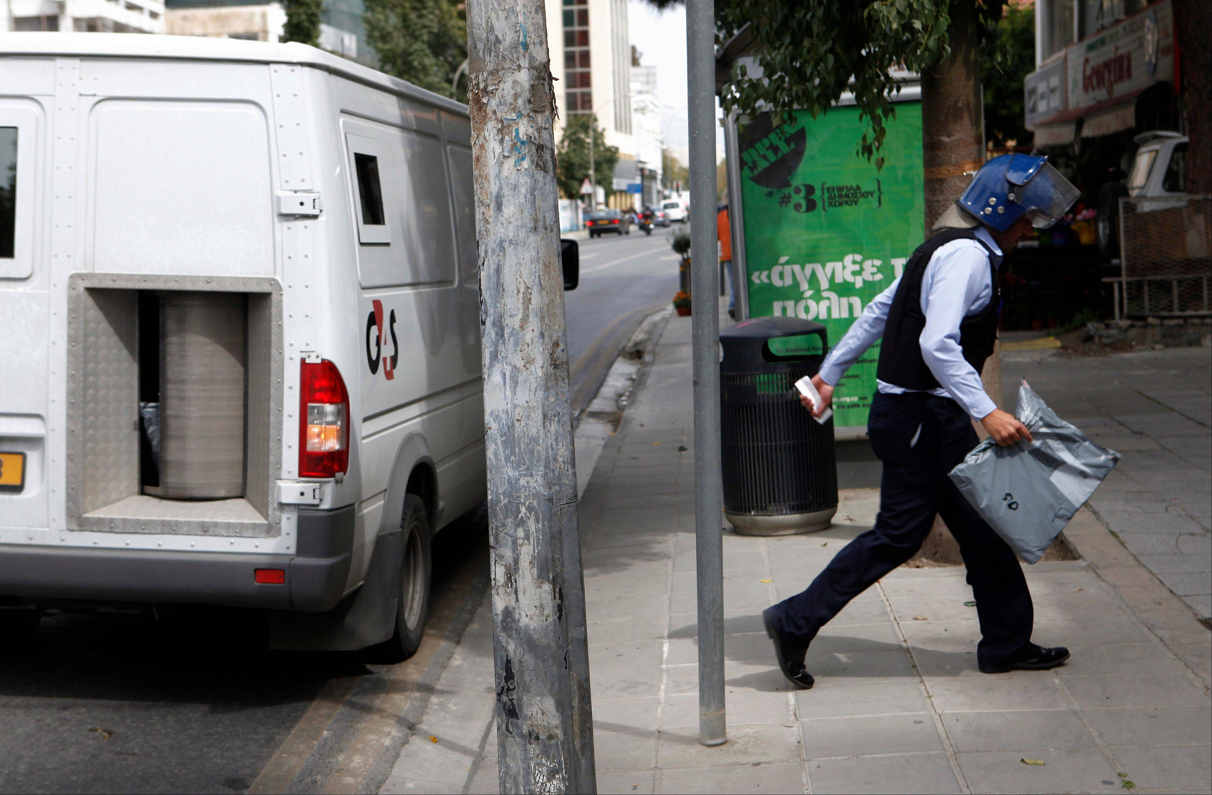 An employee of company used for collecting and transferring money carrying an envelope to a branch of Hellenic bank in capital Nicosia, Friday,