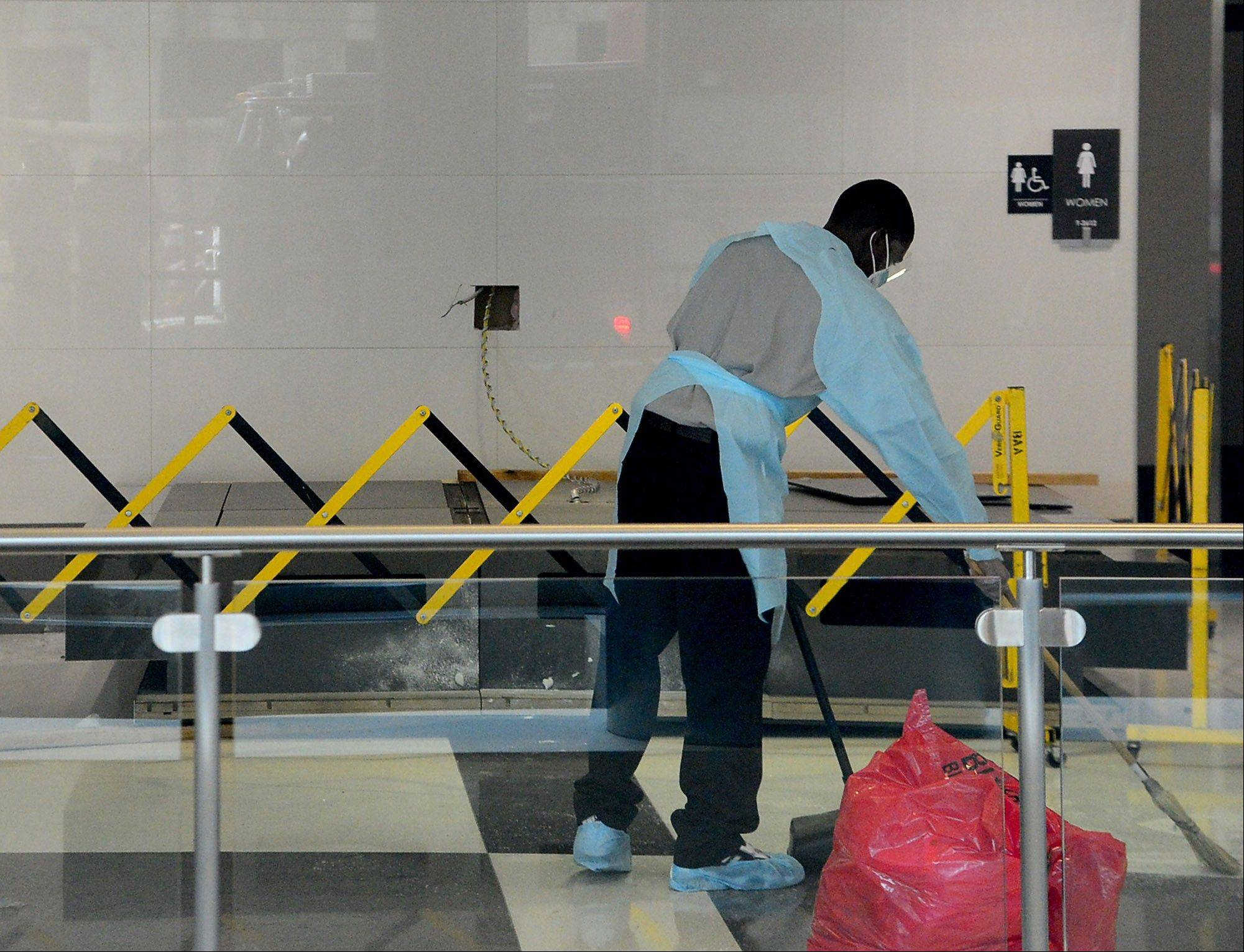 A maintenance worker sweeps up debris beside a message board sign that fell Friday on a family, killing a child and injuring the mother and two other children in the terminal at the Birmingham-Shuttlesworth International Airport in Birmingham, Ala.