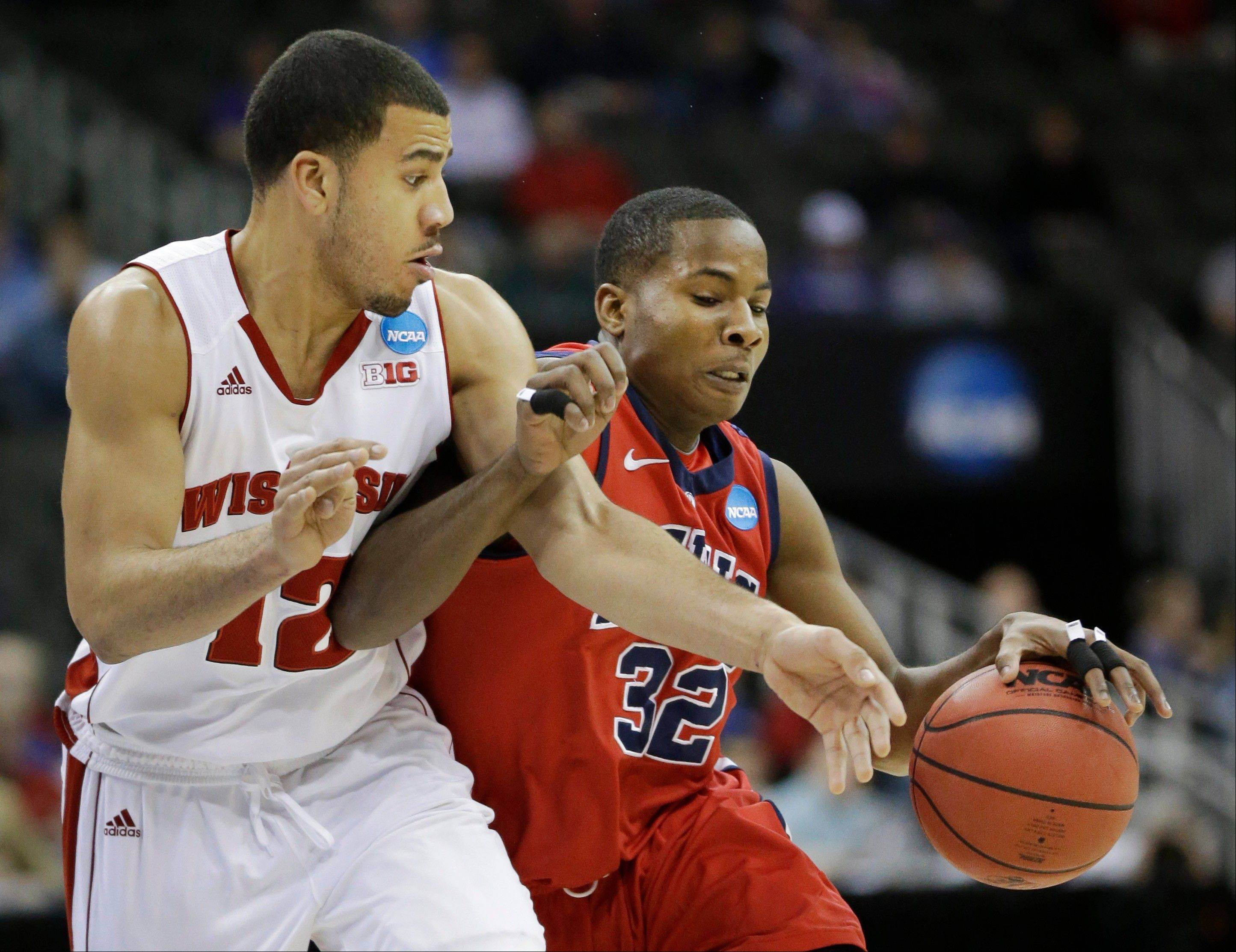 Mississippi guard Jarvis Summers (32) is fouled by Wisconsin guard Traevon Jackson (12) Friday during the first half of a second round game in the NCAA tournament at the Sprint Center in Kansas City, Mo.