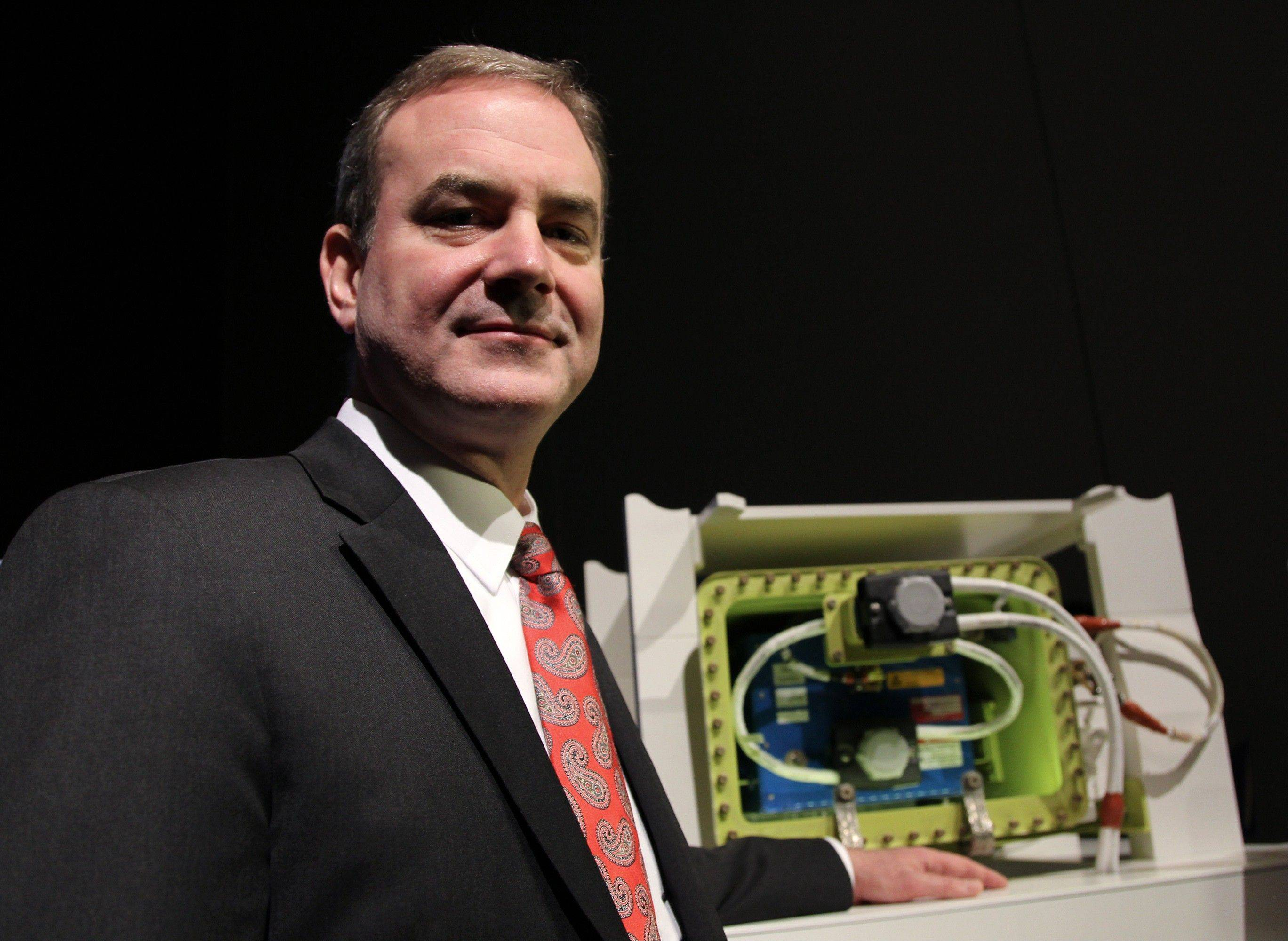 Mike Sinnett, vice president at Boeing Commercial Airplanes and chief project engineer of the 787 program, poses for a photograph with a model of the newly redesigned battery for Boeing Co.'s 787 Dreamliner during a news conference in Tokyo, Japan, last Friday, March 15.