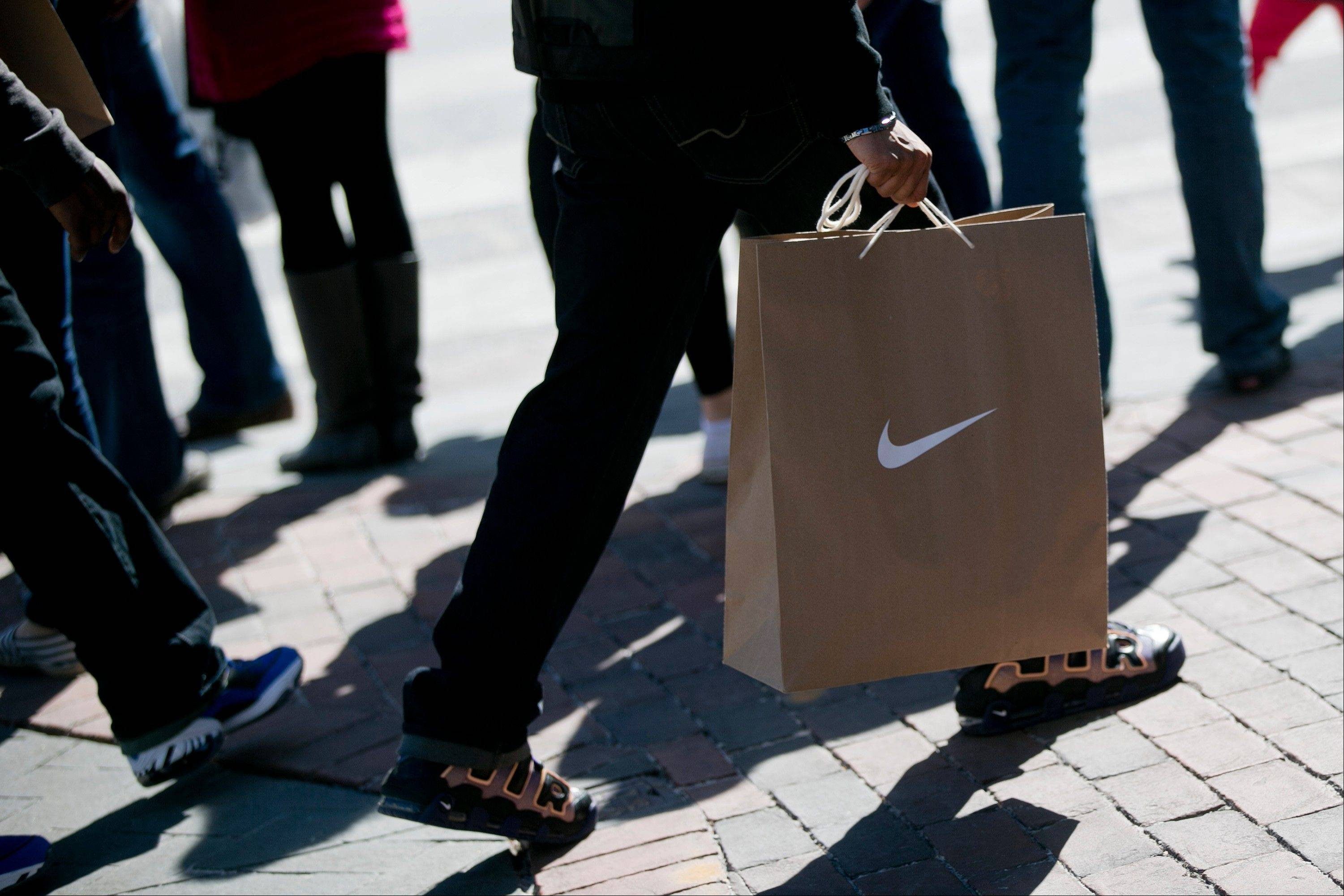 Bloomberg News/March 9A man carries a Nike Inc. shopping bag in the Georgetown neighborhood of Washington, D.C.