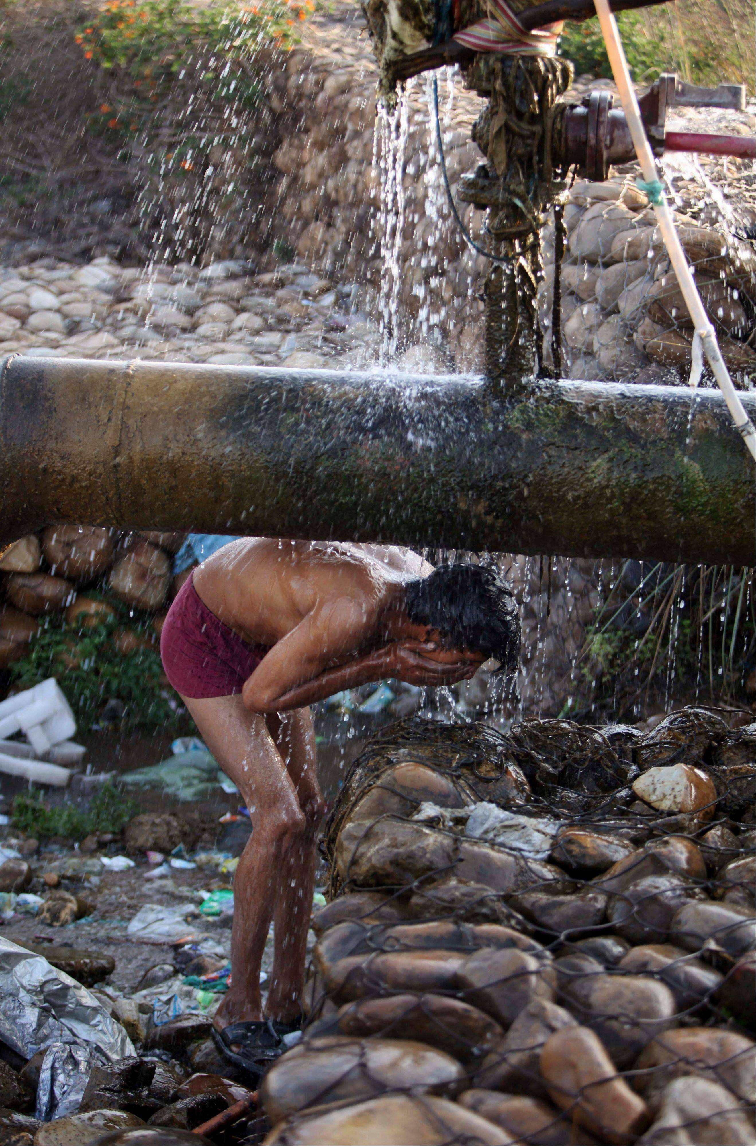 An Indian man bathes under a leaking water supply pipeline on World Water Day on the outskirts of Jammu, India, Friday.