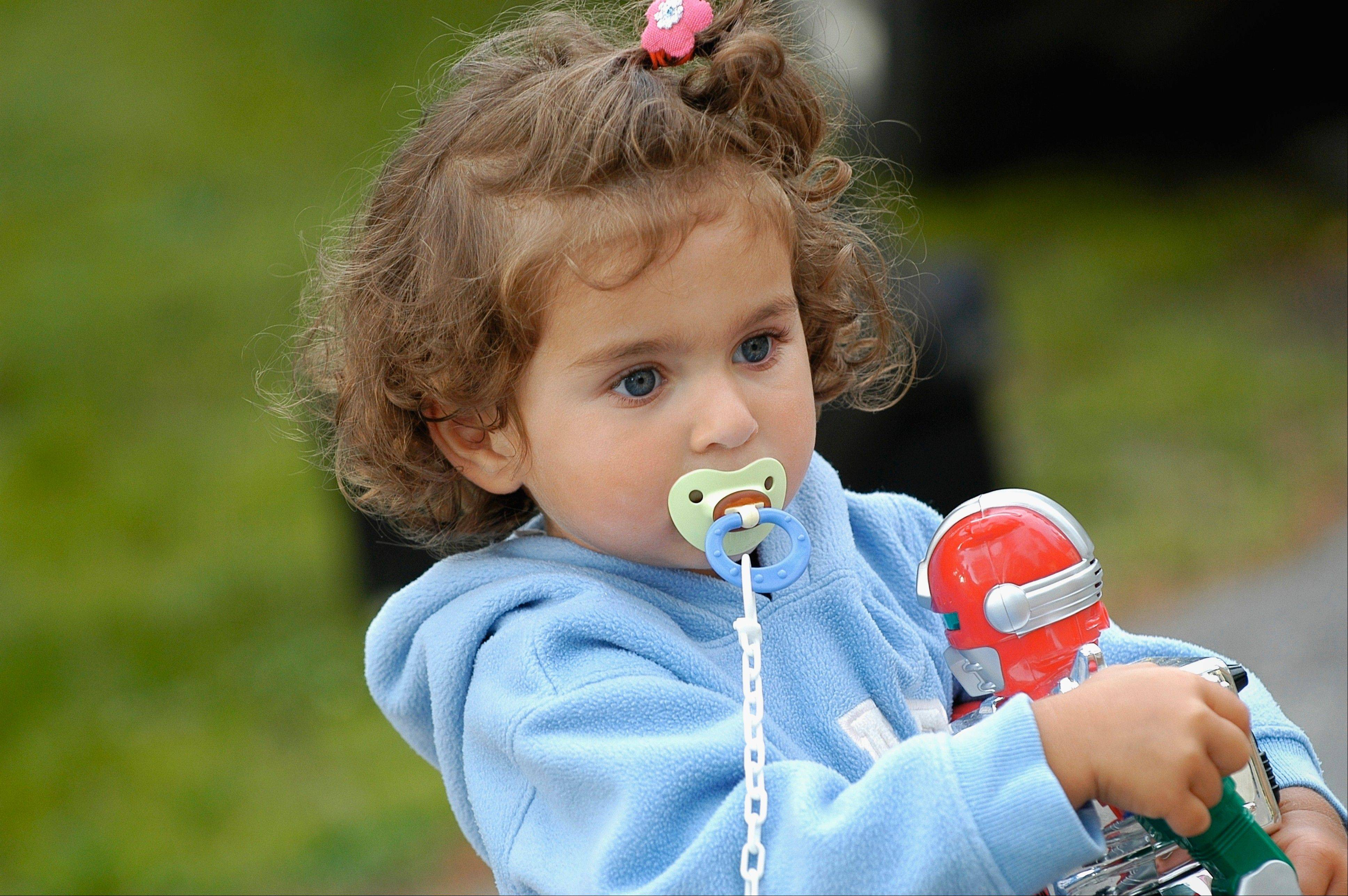 Close-up of a young girl with a pacifier in a garden.