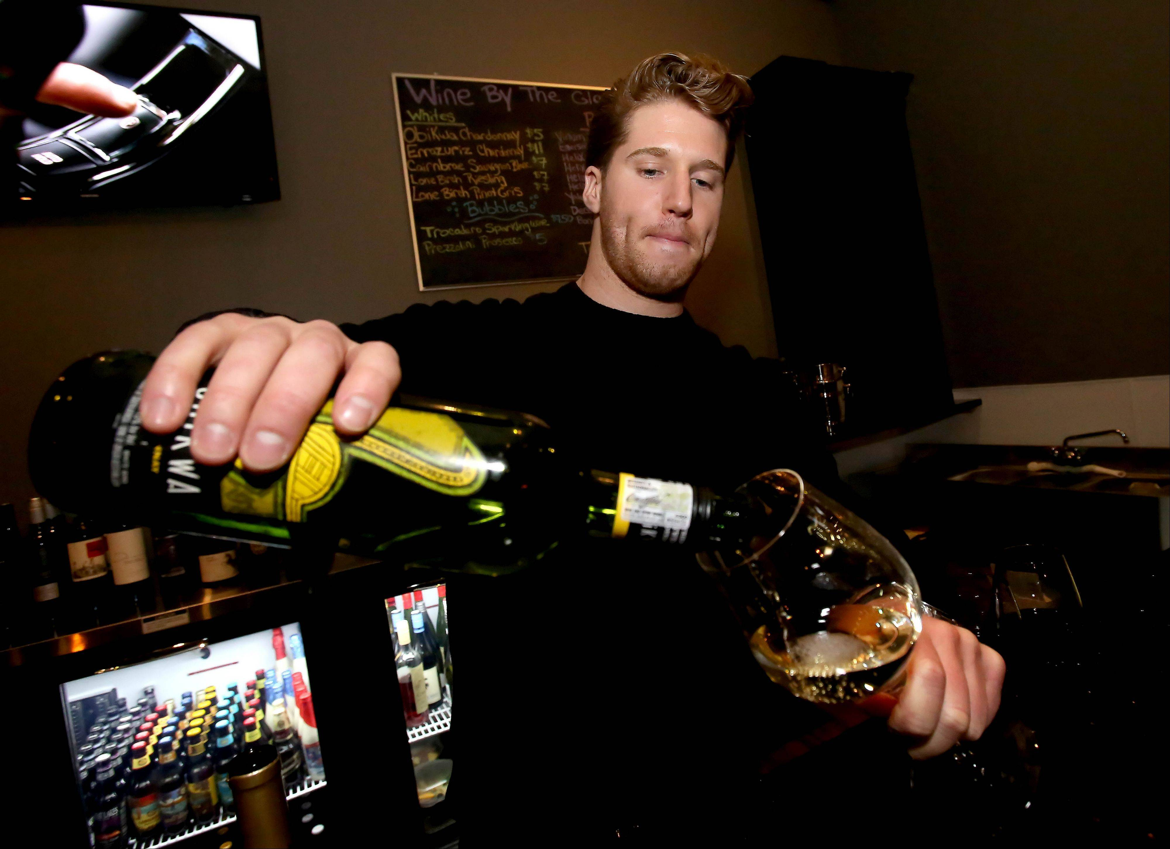 Bartender Kelly Williams pours a glass of wine at The Vino Cellar in Lombard.