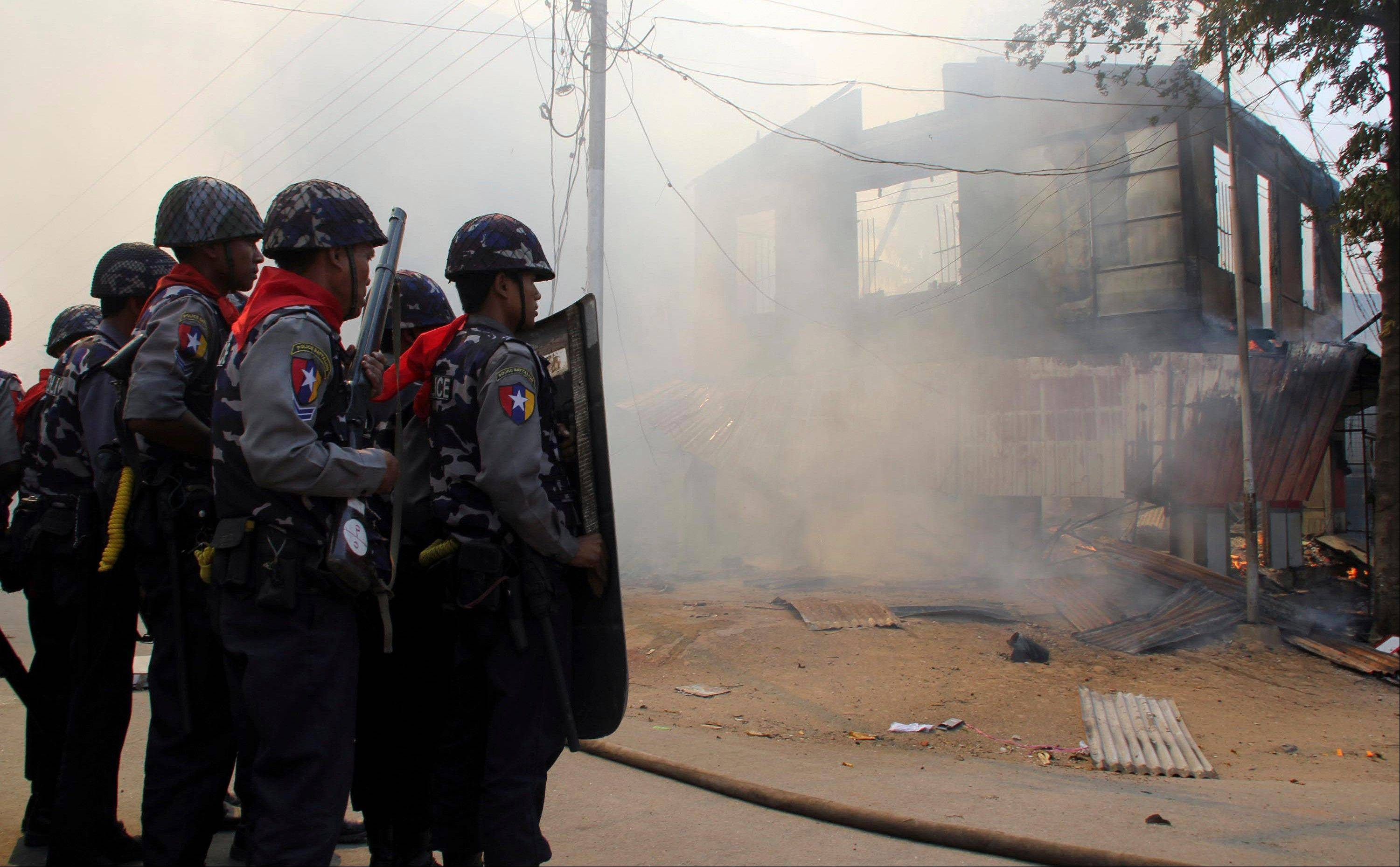 Armed Myanmar police oficers provide security Thursday around a smoldering building following ethnic unrest between Buddhists and Muslims in Meikhtila, Myanmar.