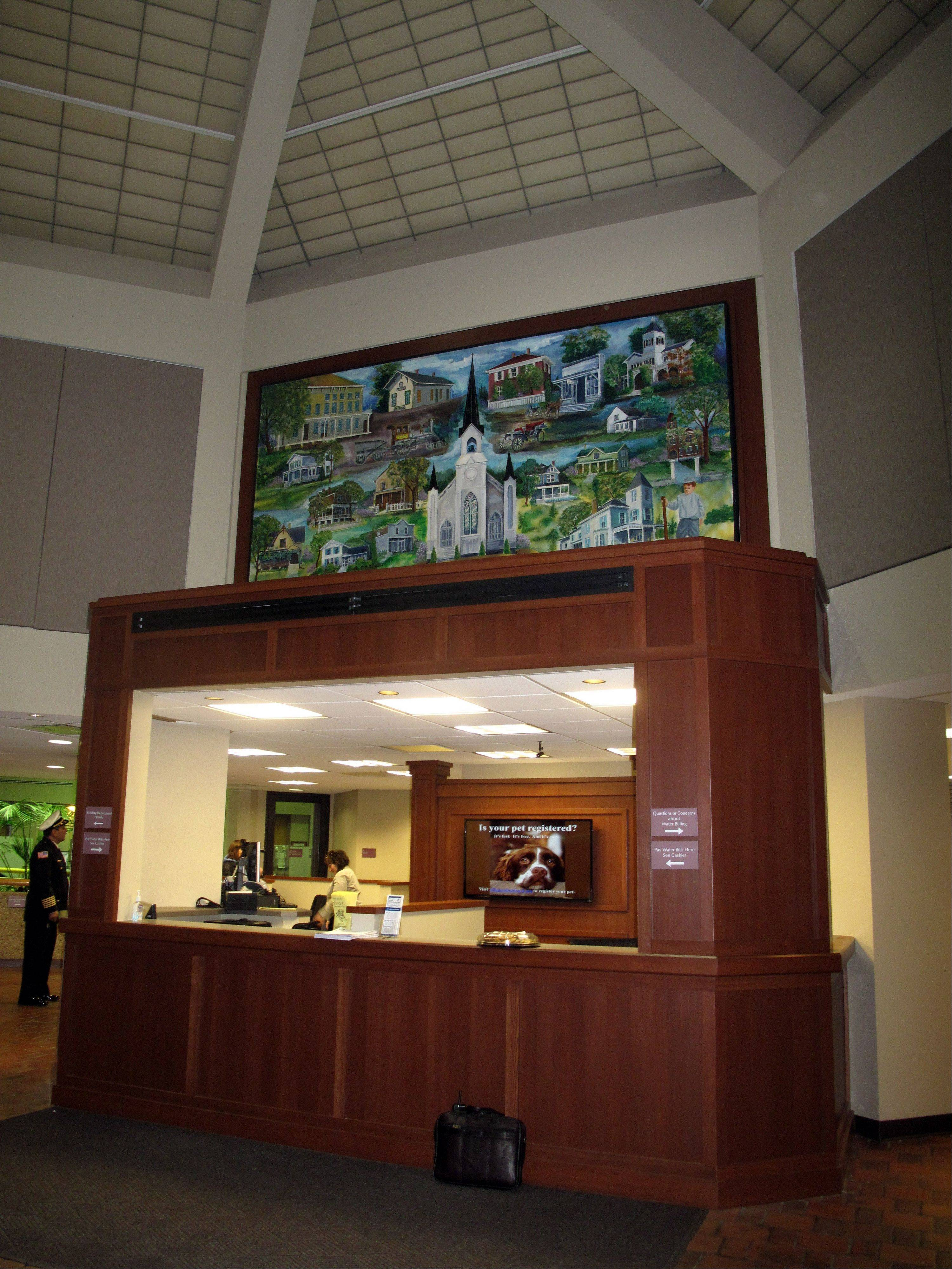 A lower counter in a cherry wood finish, two new work stations and a LED screen displaying village events were added to the front desk at Lombard village hall during a recently completed $65,000 renovation. The painting above the desk also received a facelift.