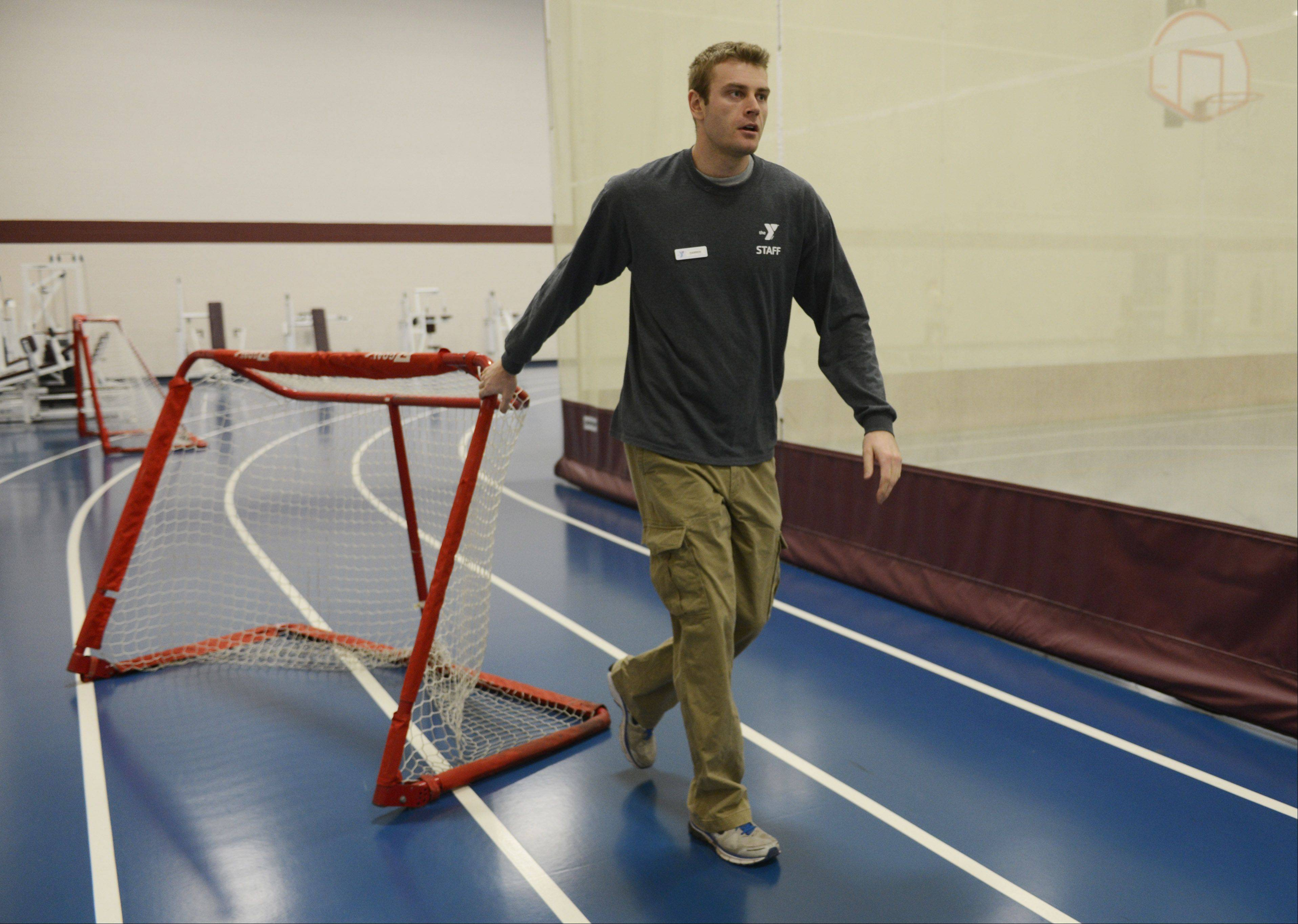 "Darren Niedermeyer, youth sports coordinator at the Campanelli YMCA in Schaumburg, moves a goal onto a court prior to leading children in a game of floor hockey during a session of ""Sporties for Shorties."""
