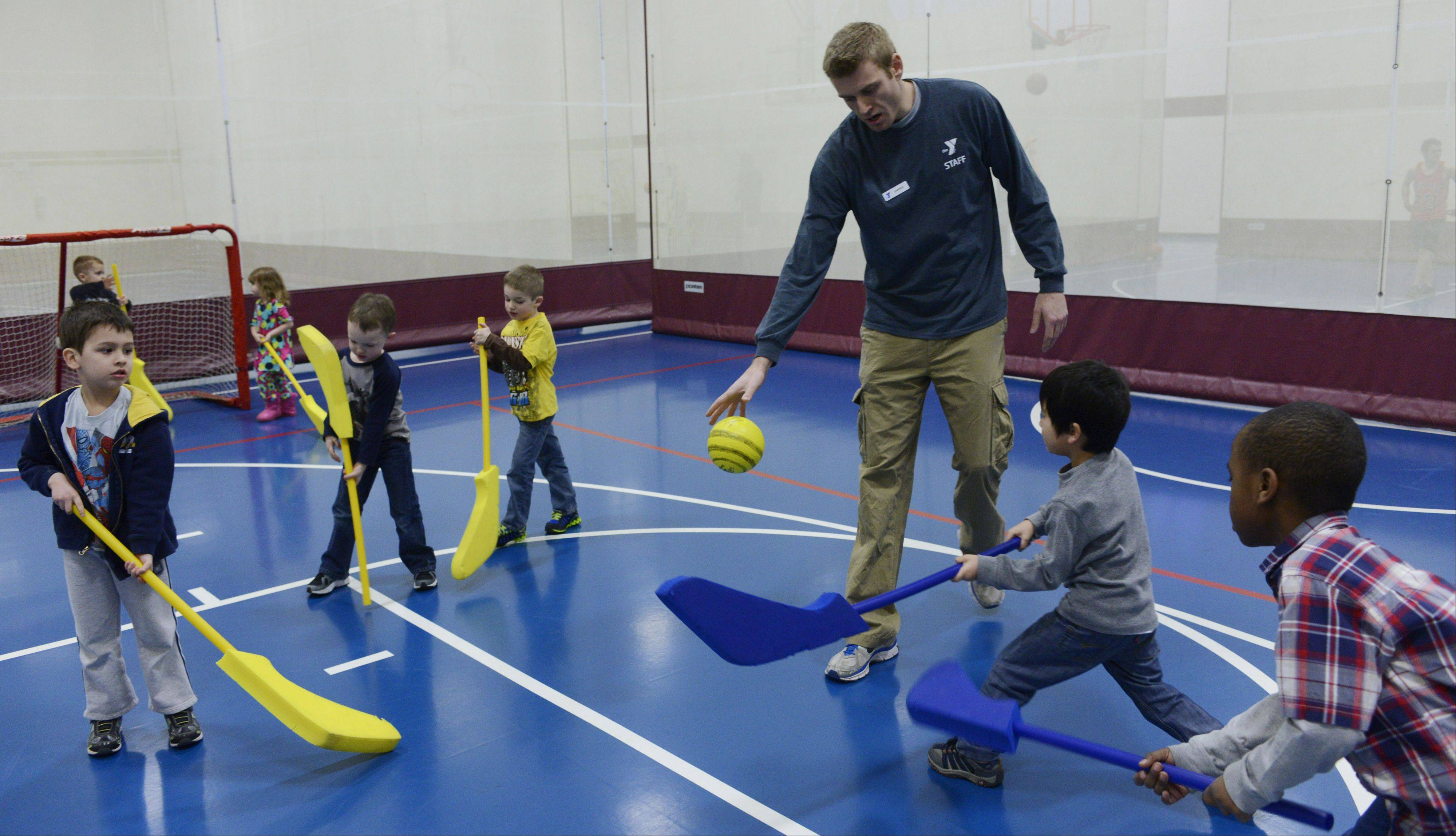 "Darren Niedermeyer, youth sports coordinator at the Campanelli YMCA in Schaumburg, leads children in a game of floor hockey during a session of ""Sporties for Shorties."""