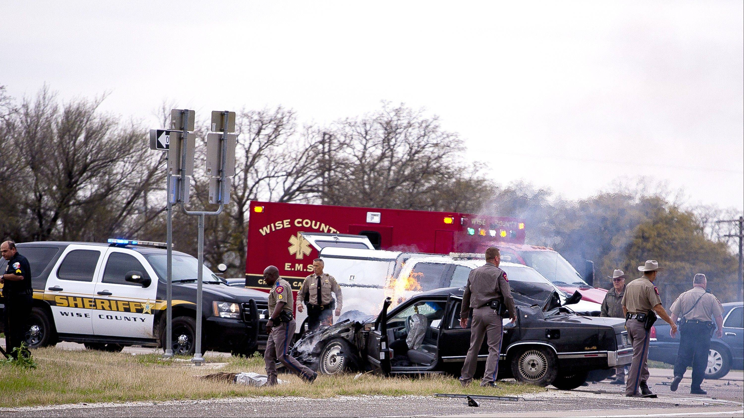 Emergency personnel on the scene of a crash and shootout with police involving the driver of a black Cadillac with Colorado plates in Decatur, Texas, Thursday, March 21, 2013. Investigators from three Colorado police agencies rushed to Texas to determine if a man identified as a parolee, who was critically wounded by Texas police after a harrowing 100-mph car chase, is linked to the slaying of Colorado's state prisons chief.