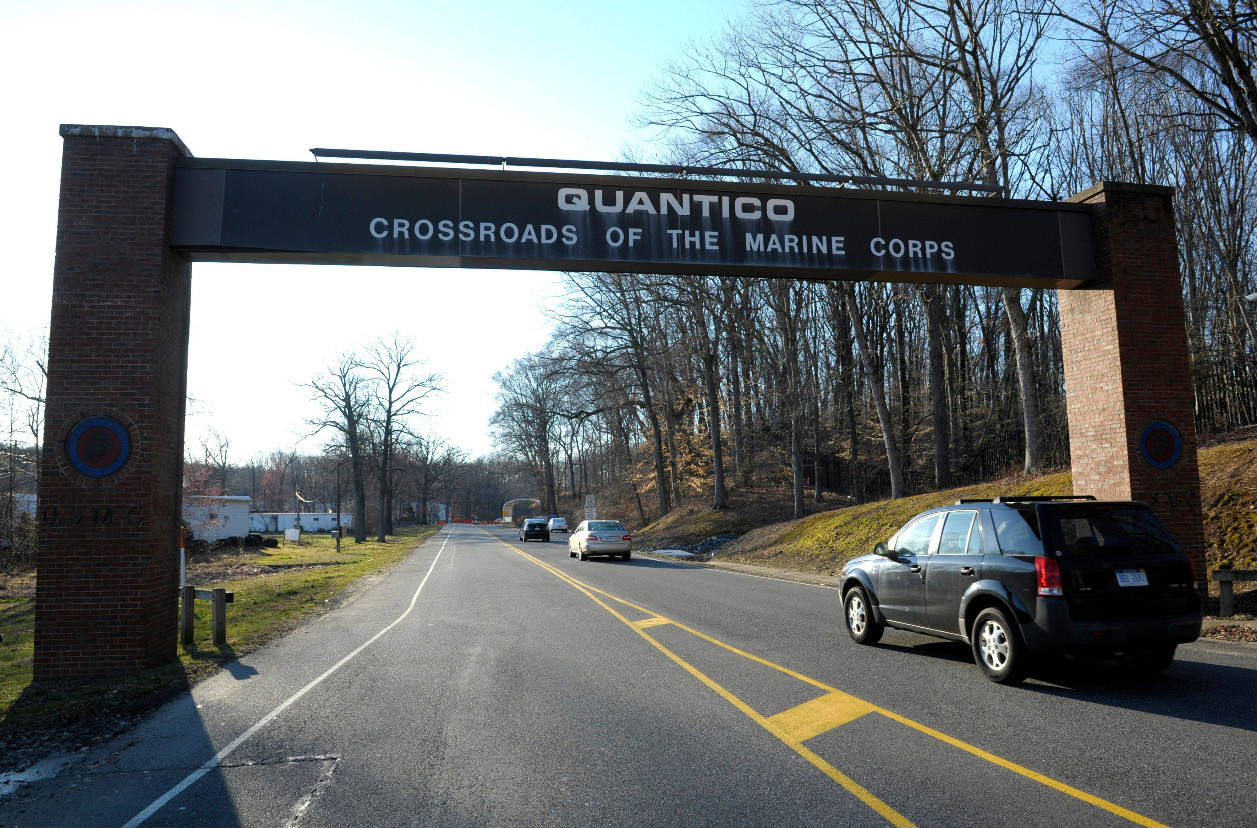 Cars pass under a sign at the entrance to the main gate at Quantico Marine Corps Base in Quantico, Va., Friday, March 22, 2013. A Marine killed a male and female colleague in a shooting at a base in northern Virginia before killing himself, officials said early Friday.