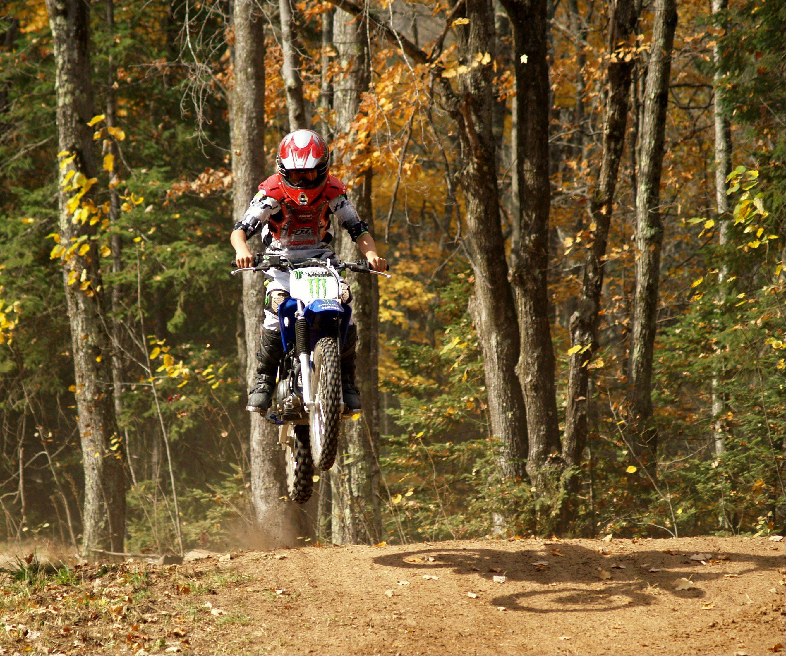 Nick Tinaglia gets some air while dirt biking on trails in Mountain, Wisconsin.