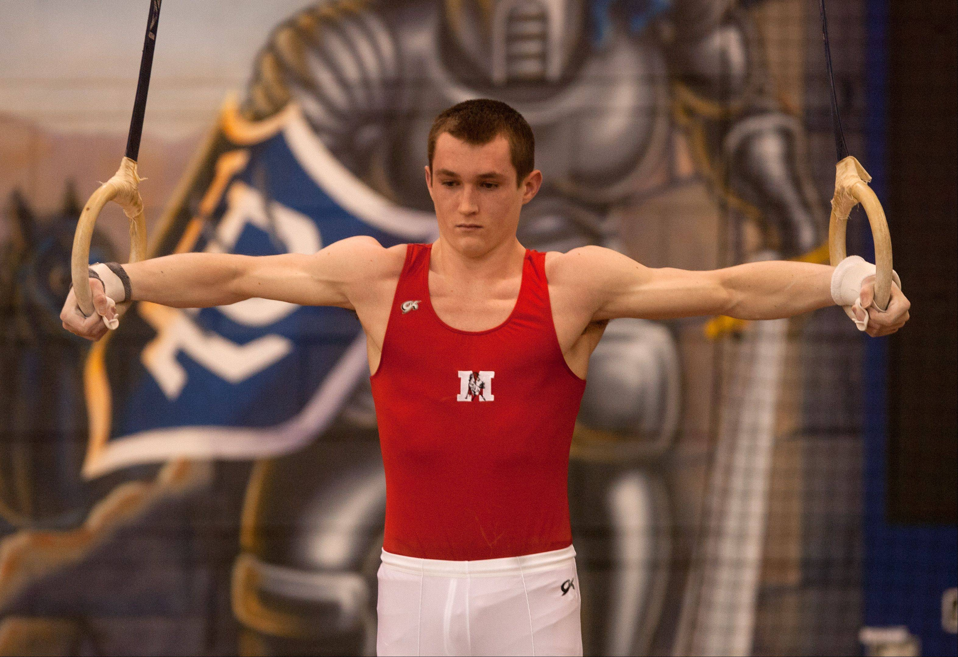 Mundelein's Cameron Mueller performs his still rings routine during the Lake Park High School Ralph Krupke Boys Gymnastics Invitational.