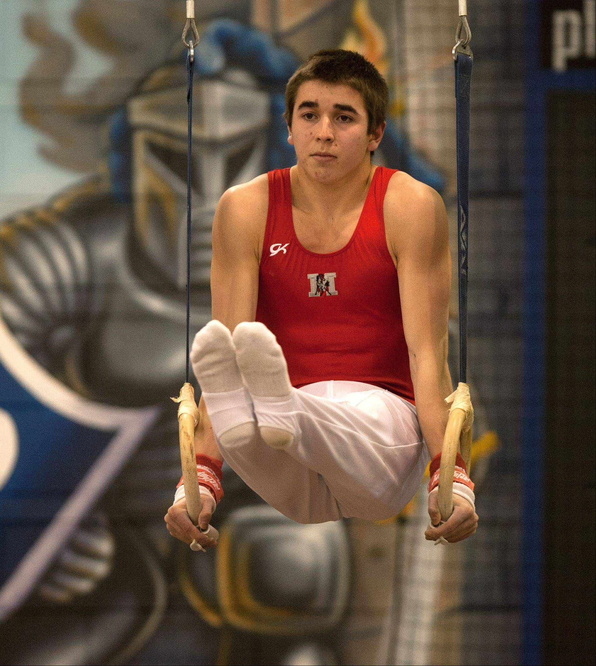 Mundelein's Colin McCarthy performs his still rings routine during the Lake Park High School Ralph Krupke Boys Gymnastics Invitational.