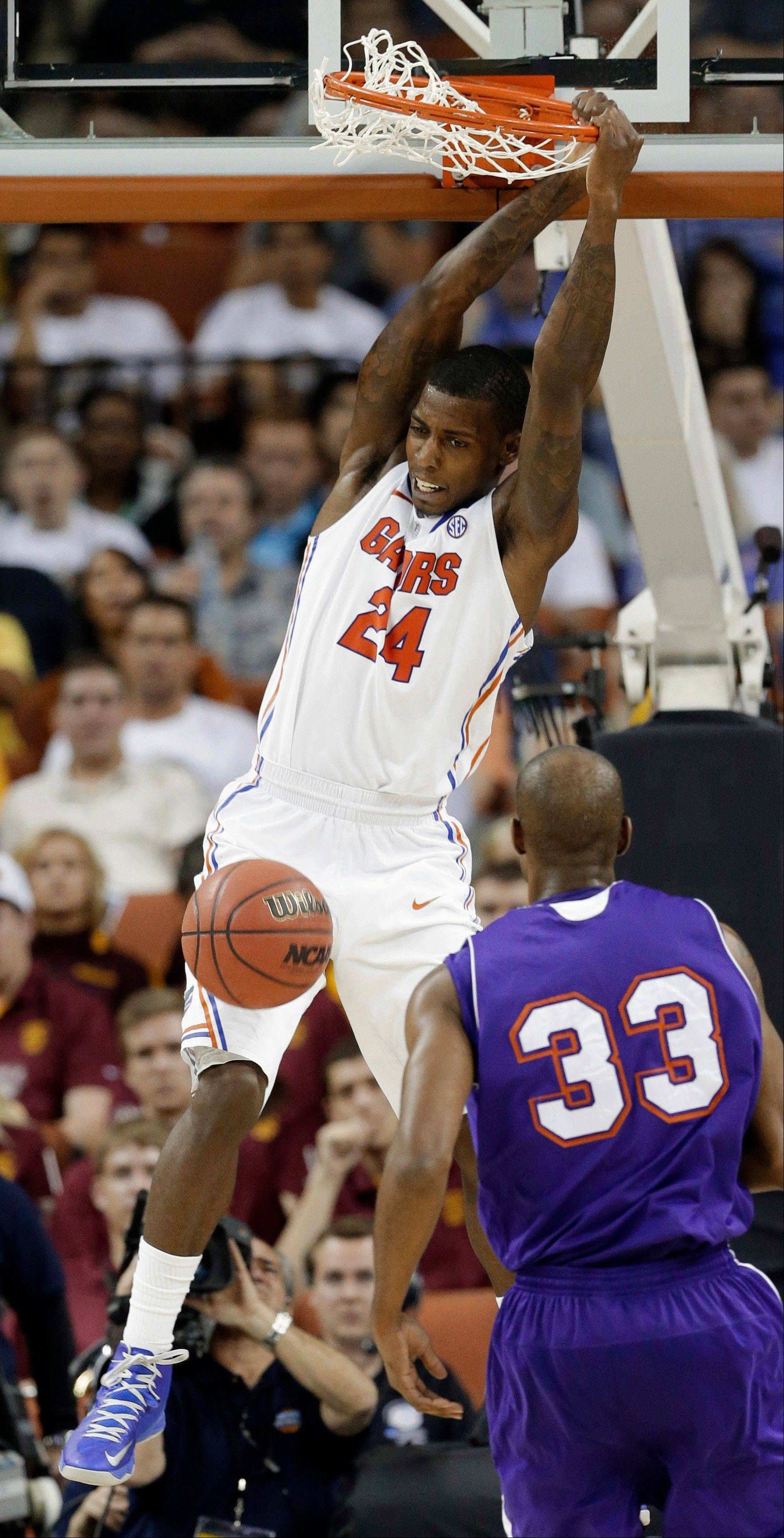 Florida's Casey Prather (24) hangs on the rim after dunkingas Northwestern State's James Hulbin (33) watches during the second half of a second-round game of the NCAA men's college basketball tournament Friday, March 22, 2013, in Austin, Texas. Florida won 79-47.