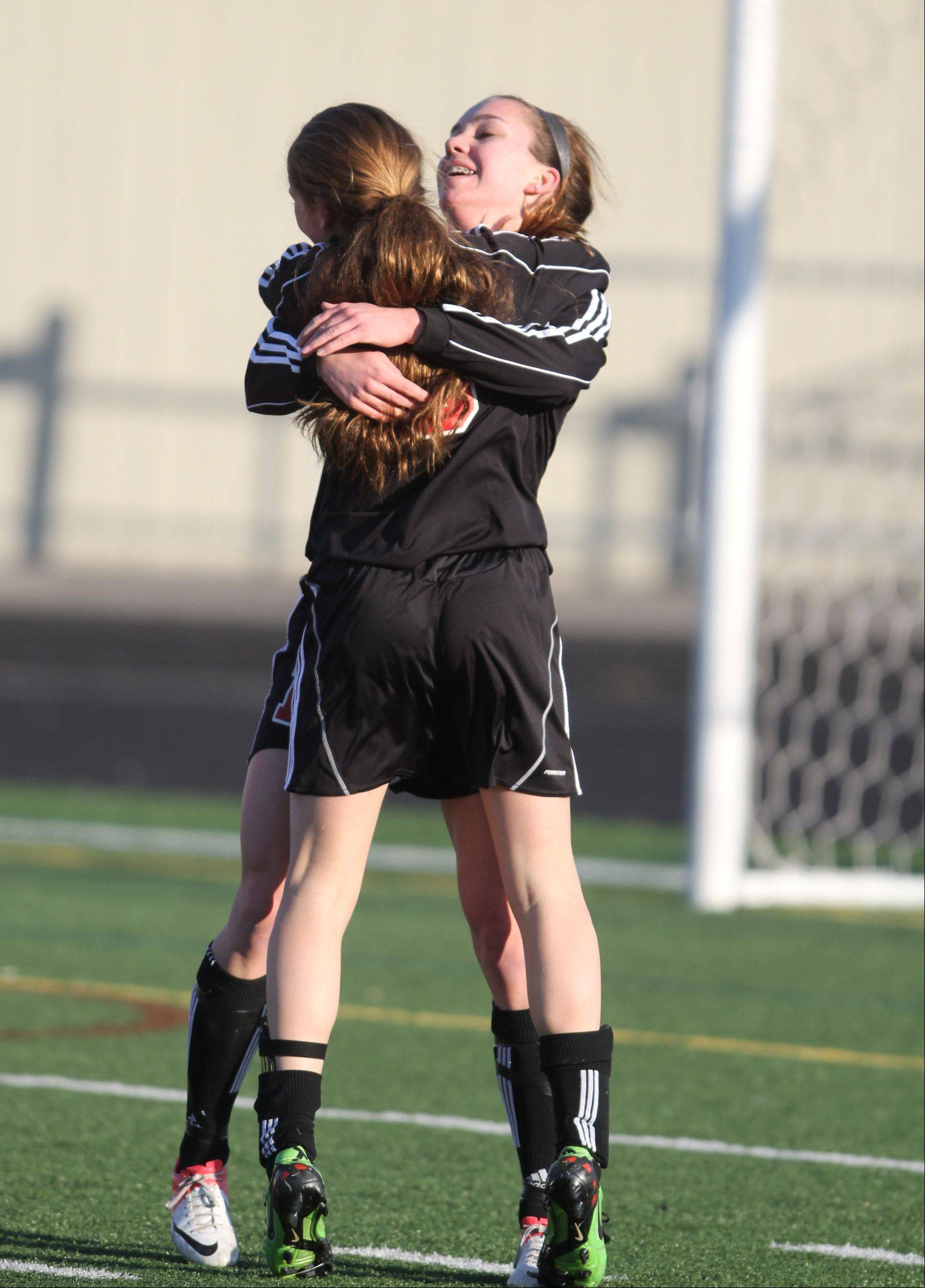 Barrington's Jenna Szczensny, facing forward, gets a hug from Kelsey Muniz after scoring against Schaumburg at Schaumburg on Friday.