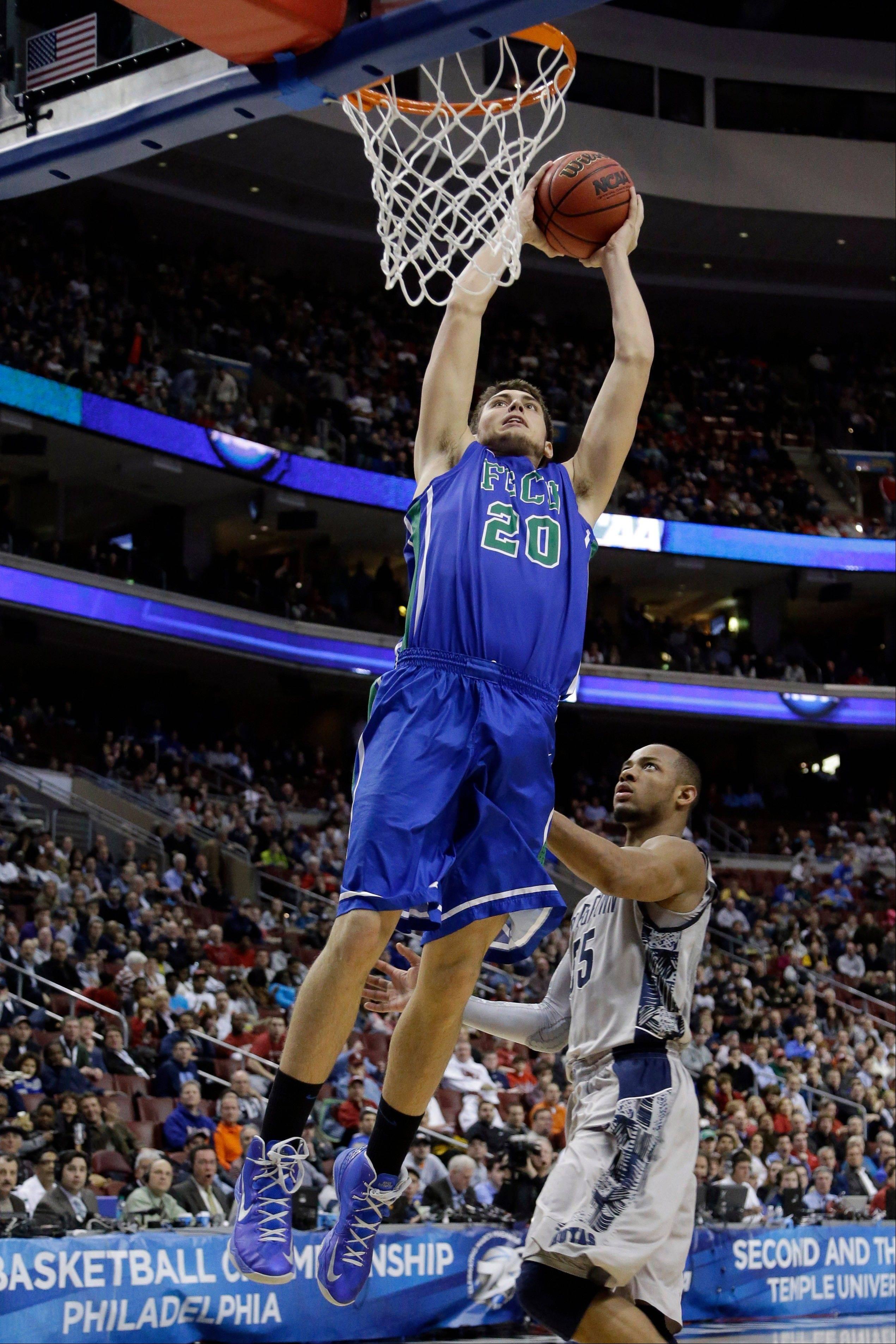 Florida Gulf Coast's Chase Fieler goes up for a dunk against Georgetown's Jabril Trawick during the second half of a second-round game of the NCAA college basketball tournament, Friday, March 22, 2013, in Philadelphia.