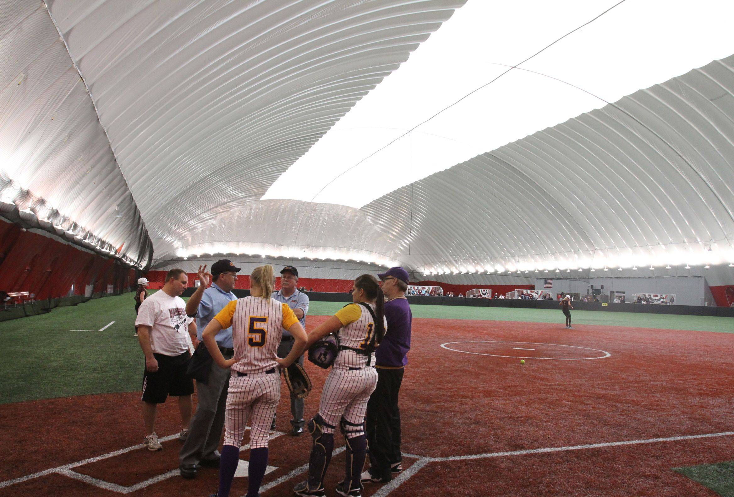 Umpires and coaches discuss the ground rules before the first pitch Friday between Wauconda and Marengo at The Dome in Rosemont.