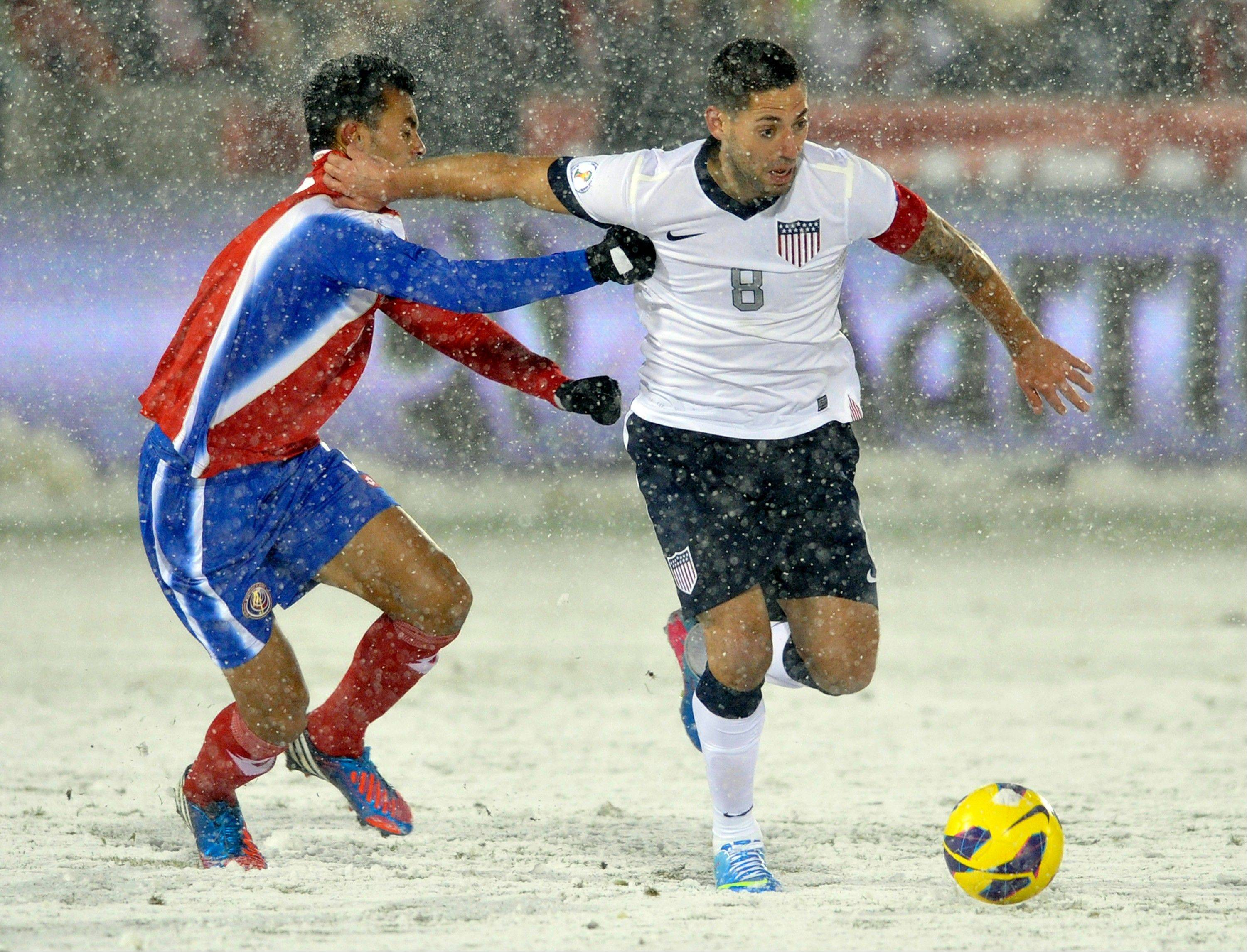 Costa Rica defender Giancarlo Gonzalez, left, pulls the jersey of United States forward Clint Dempsey (8) during the first half of a World Cup qualifier soccer match in Commerce City, Colo., Friday, March 22, 2013.