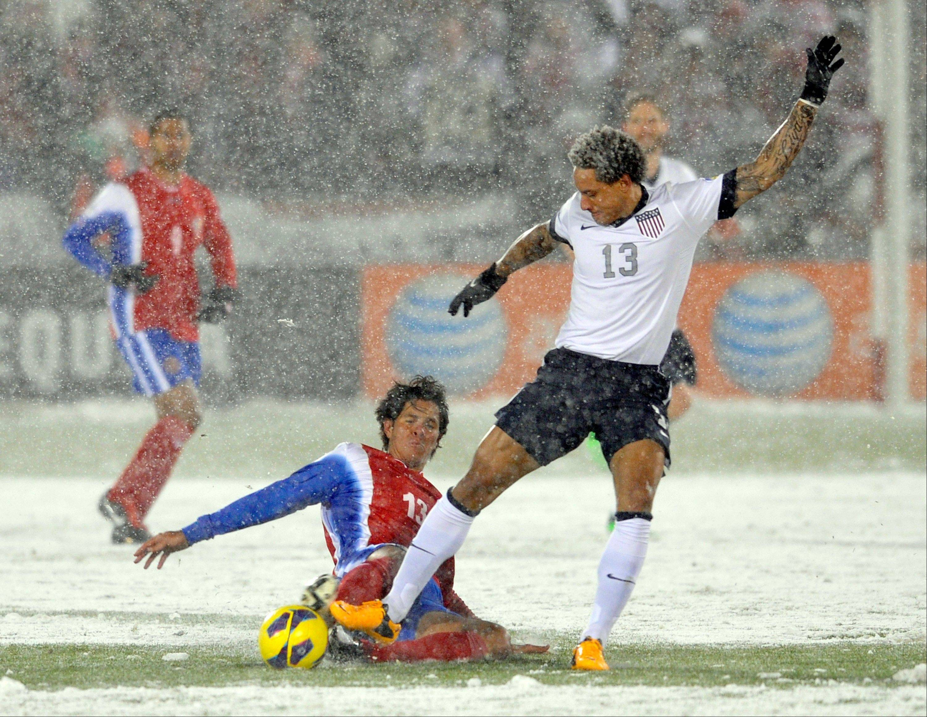 Costa Rica midfielder Ariel Rodgriguez, front left, tackles United States midfielder Jermaine Jones, right, during the first half of a World Cup qualifier soccer match in Commerce City, Colo., Friday, March 22, 2013.