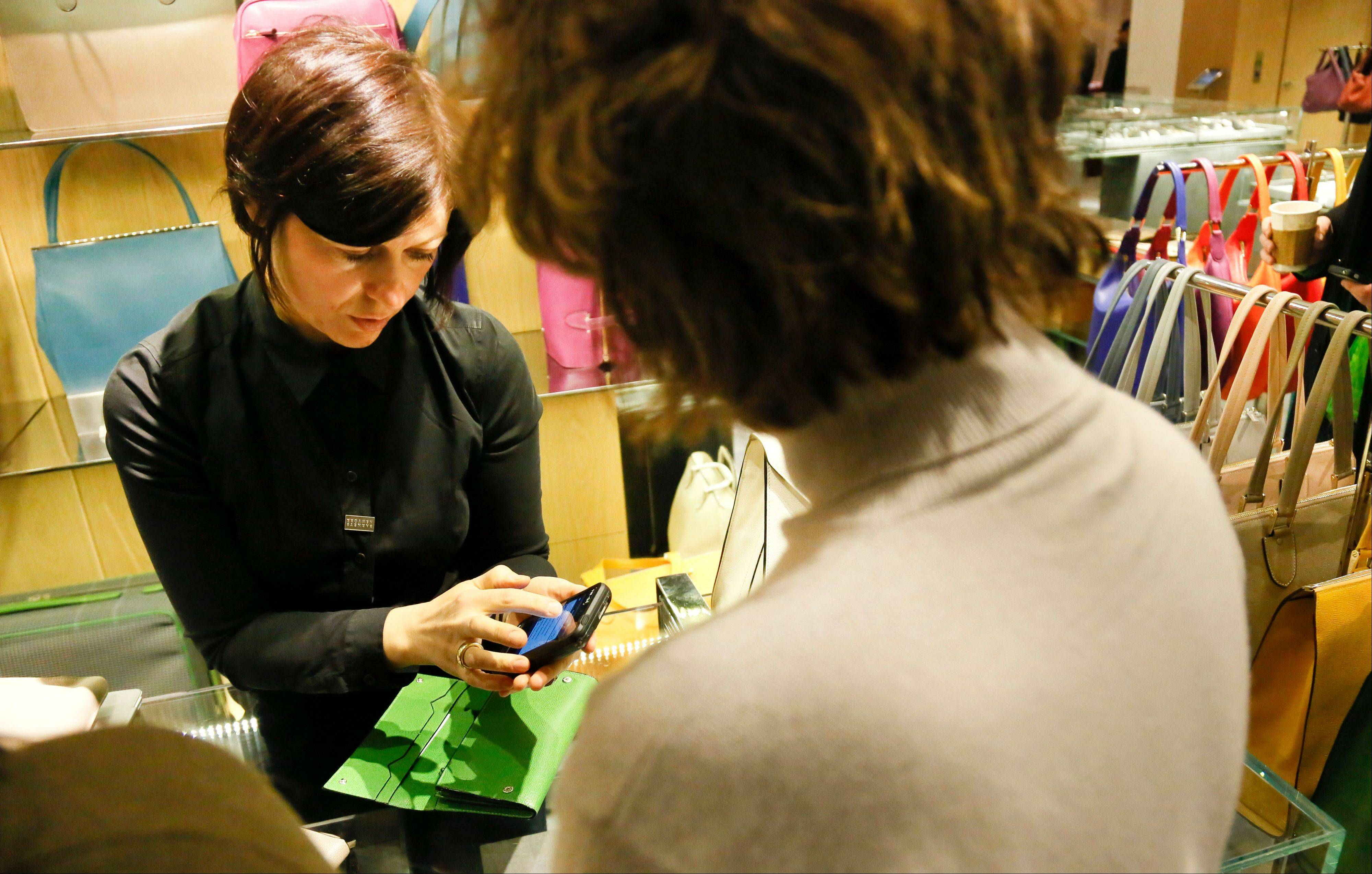 A sales staff member at Barneys New York uses an iPod Touch to help a customer make a purchase, in New York. Stores across the country are ditching the old-fashioned, clunky cash registers and instead having salespeople � and shoppers themselves � checkout on smartphones and tablet computers.