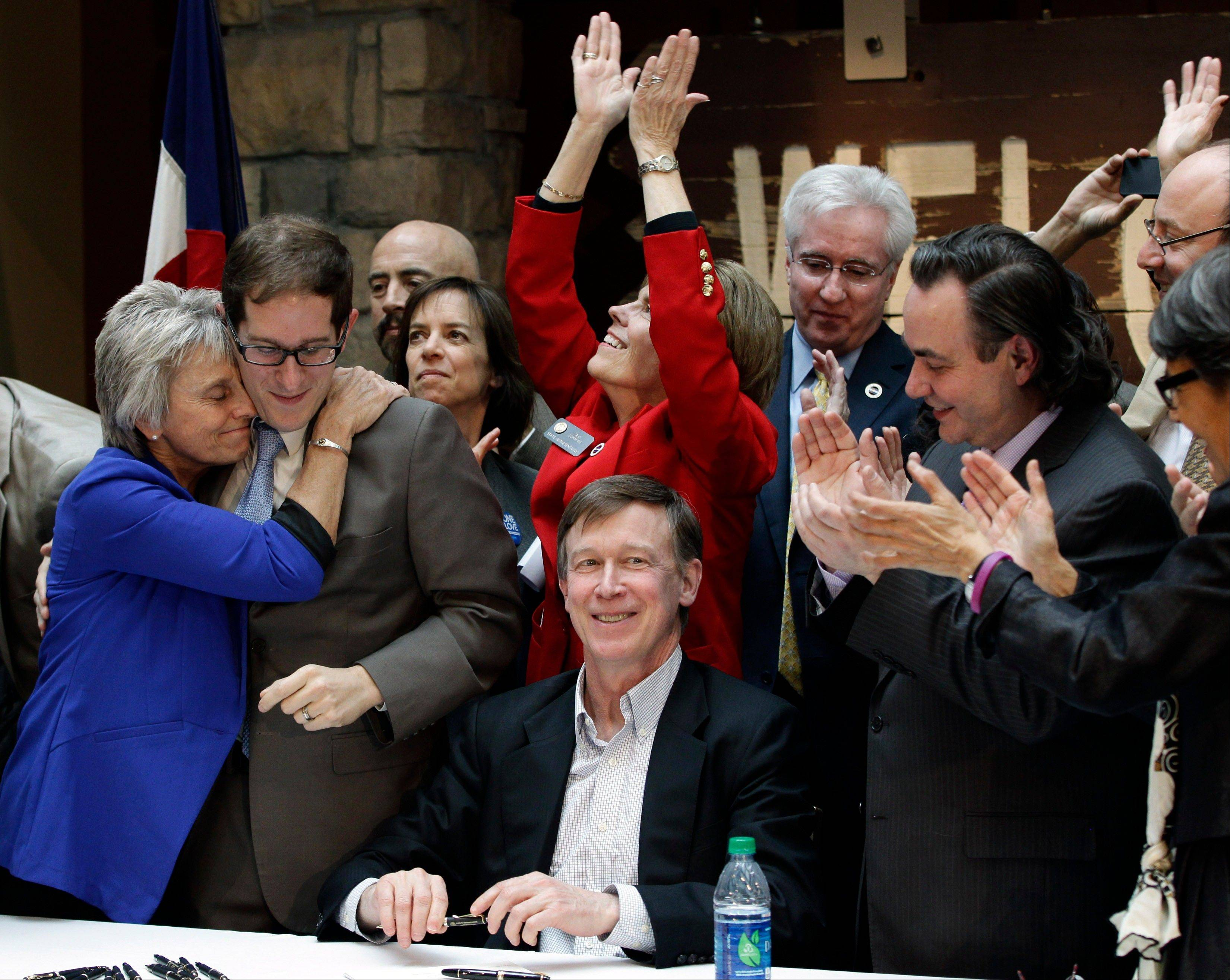 Rep. Joann Ginal, left, hugs Rep. Mark Ferrandino, as others applaud after Colorado Gov. John Hickenlooper, seated center, signed the Civil Unions Act into law Friday at the Colorado History Museum in Denver, Colo.
