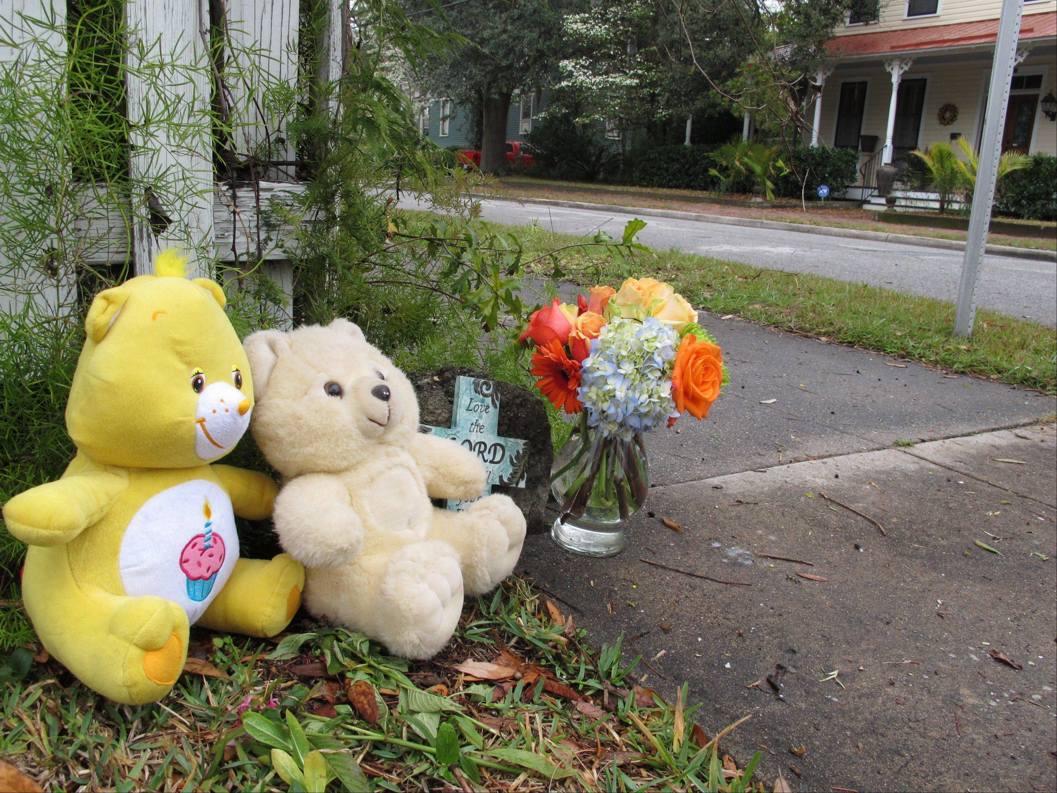 Two teddy bears, a commemorative cross and a vase of flowers sit on a street corner Saturday in Brunswick, Ga., near where a 13-month-old baby was fatally shot.