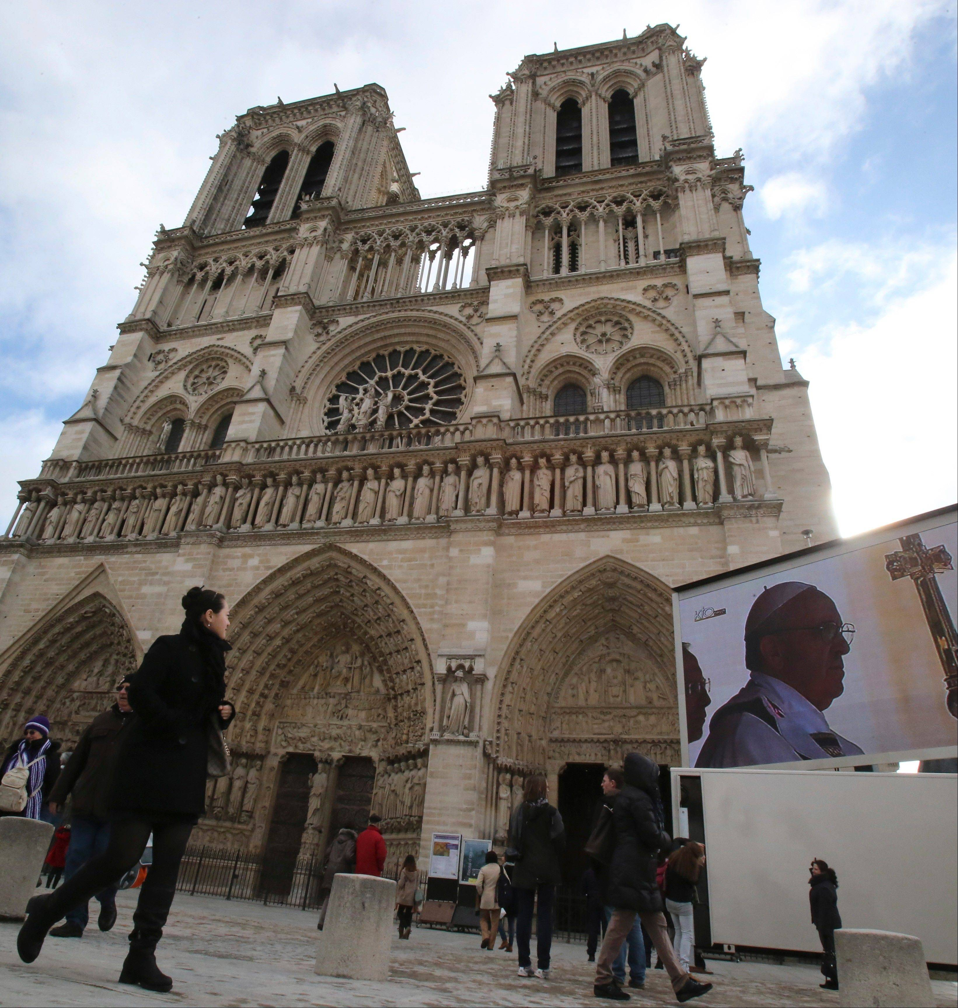 People watch the inauguration of Pope Francis on a giant screen last Tuesday outside Notre Dame cathedral, Paris.