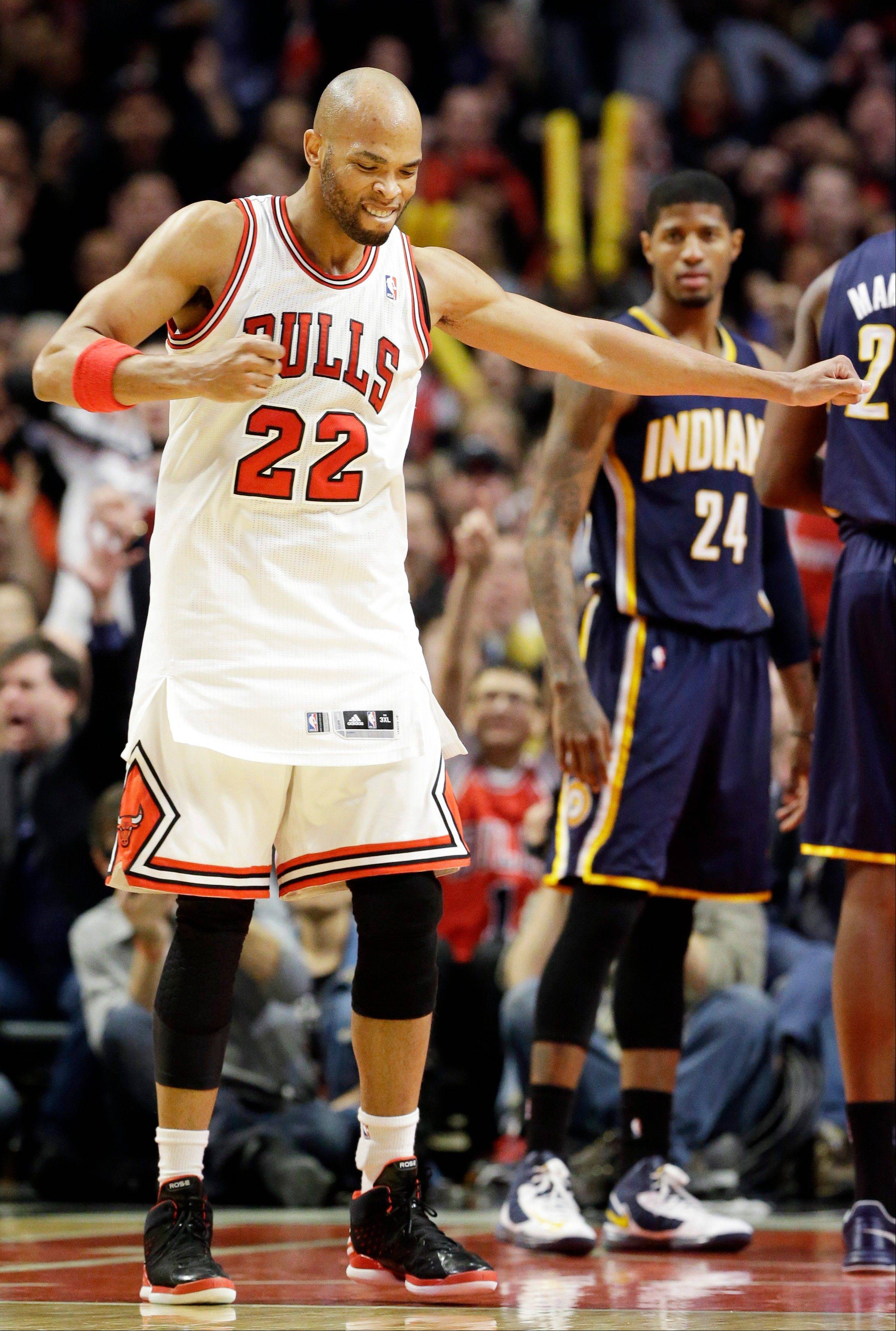 Chicago Bulls forward Taj Gibson (22) reacts after scoring a basket as Indiana Pacers forward Paul George (24) looks on during the second half of an NBA basketball game in Chicago on Saturday, March 23, 2013. The Bulls won 87-84. (AP Photo/Nam Y. Huh)