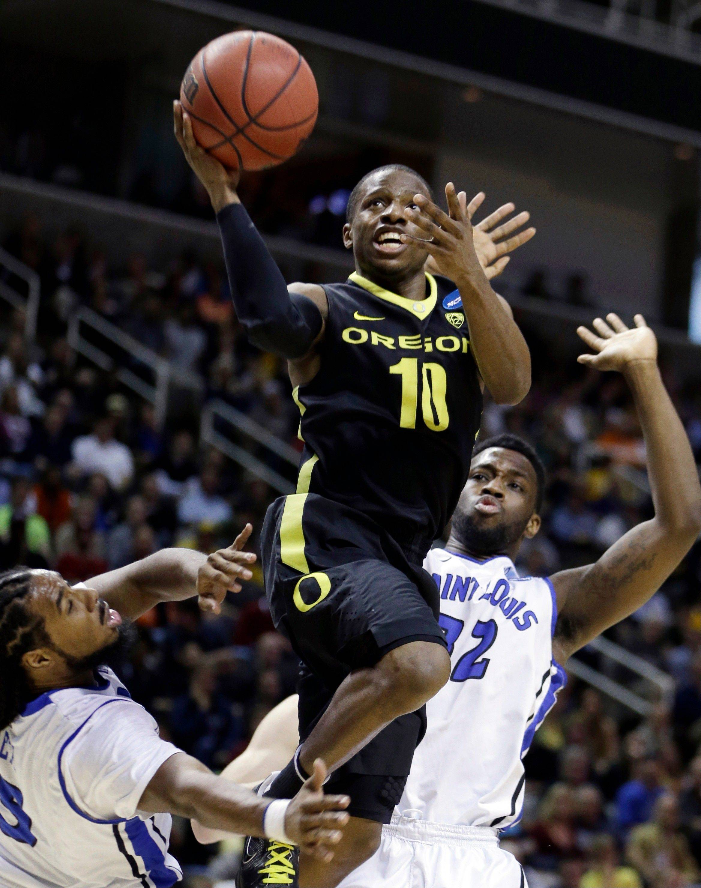 Oregon's Johnathan Loyd (10) lays up a shot over Saint Louis guard Kwamain Mitchell, left, and Cory Remekun (32) during the second half of a third-round game in the NCAA college basketball tournament Saturday, March 23, 2013, in San Jose, Calif. Oregon won the game, 74-57. (AP Photo/Ben Margot)