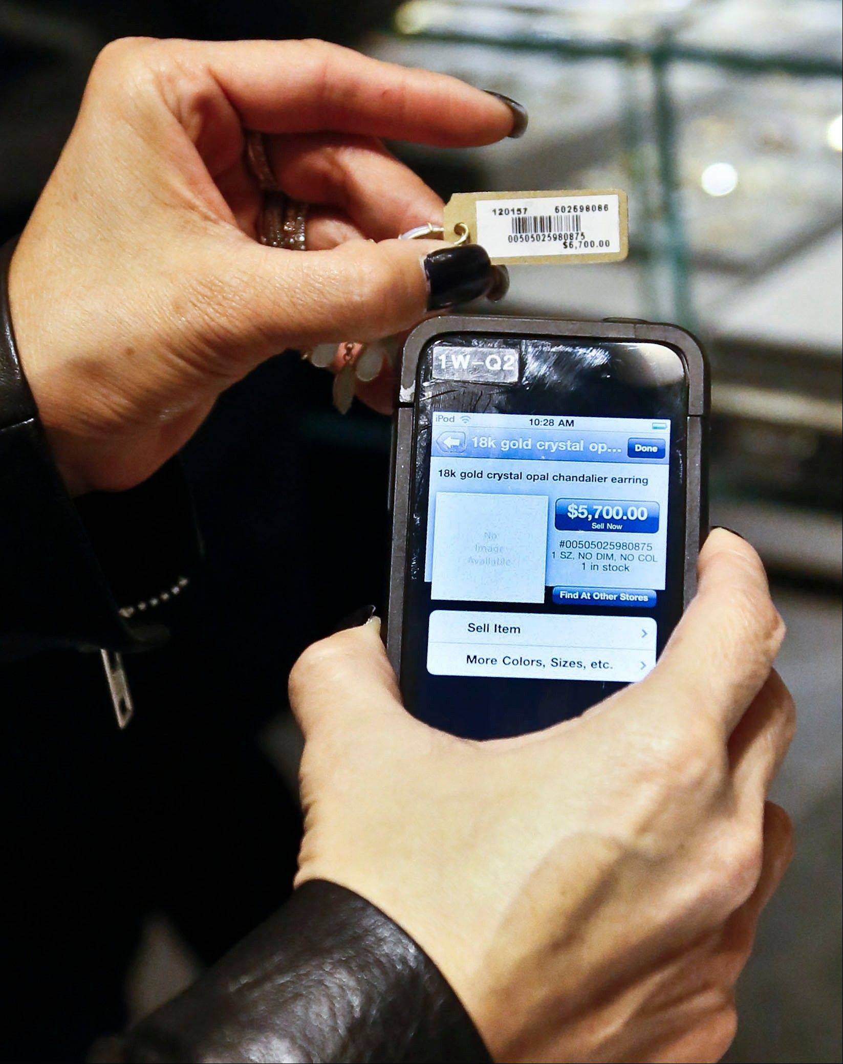 A sales staff member at Barneys New York uses an iPod Touch to help a customer make a purchase, in New York.