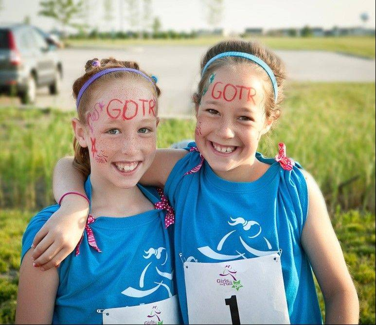 At the 5K, girls run with a buddy. Some girls, like Julia Fier, left, pick their dads to be running buddies. Running partners get in shape during a practice run, said twin Lauren Fier, right, whose buddy was the school secretary.