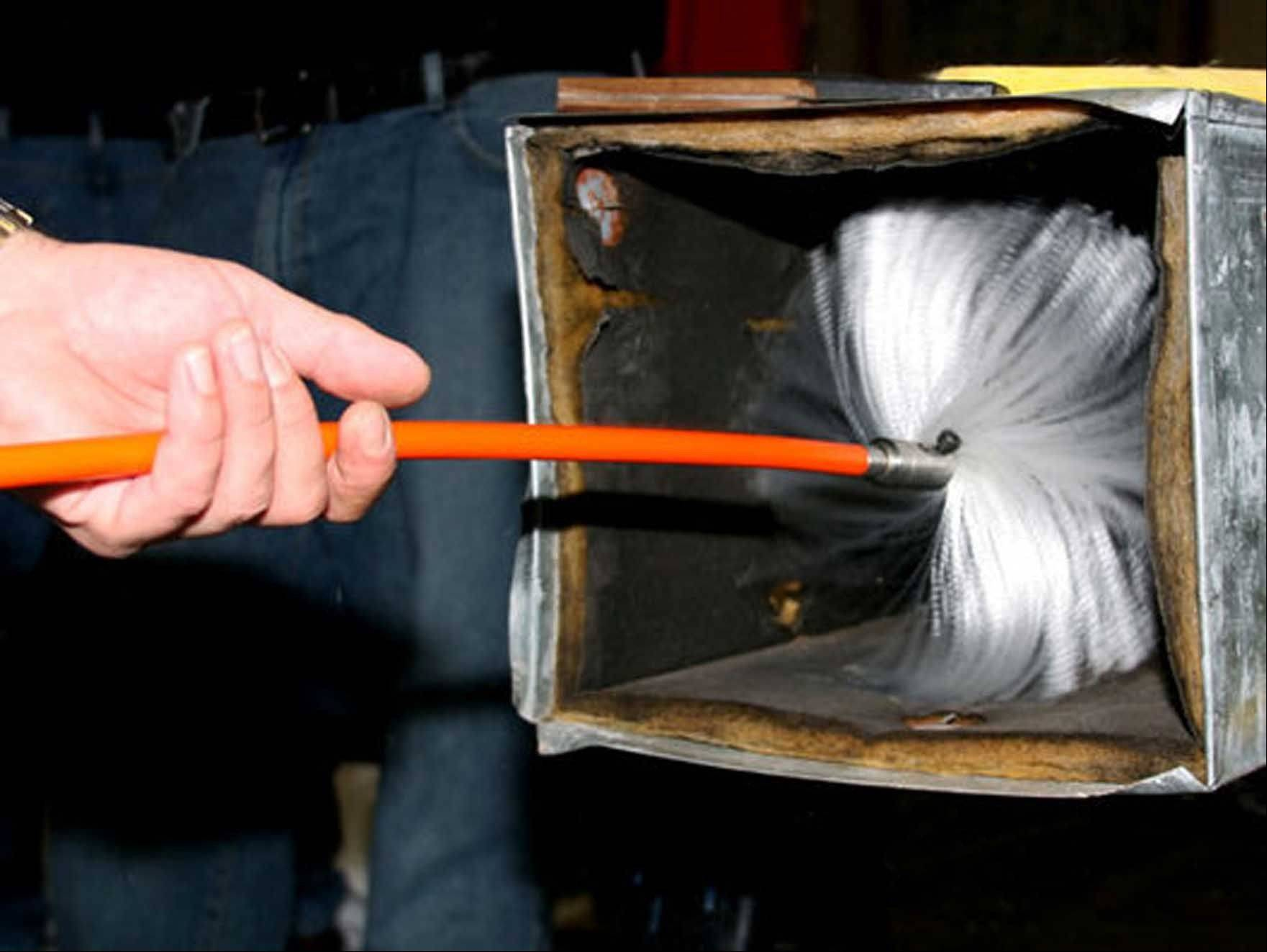 A technician uses a brush to clean ductwork. A typical cleaning costs $400 to $800.
