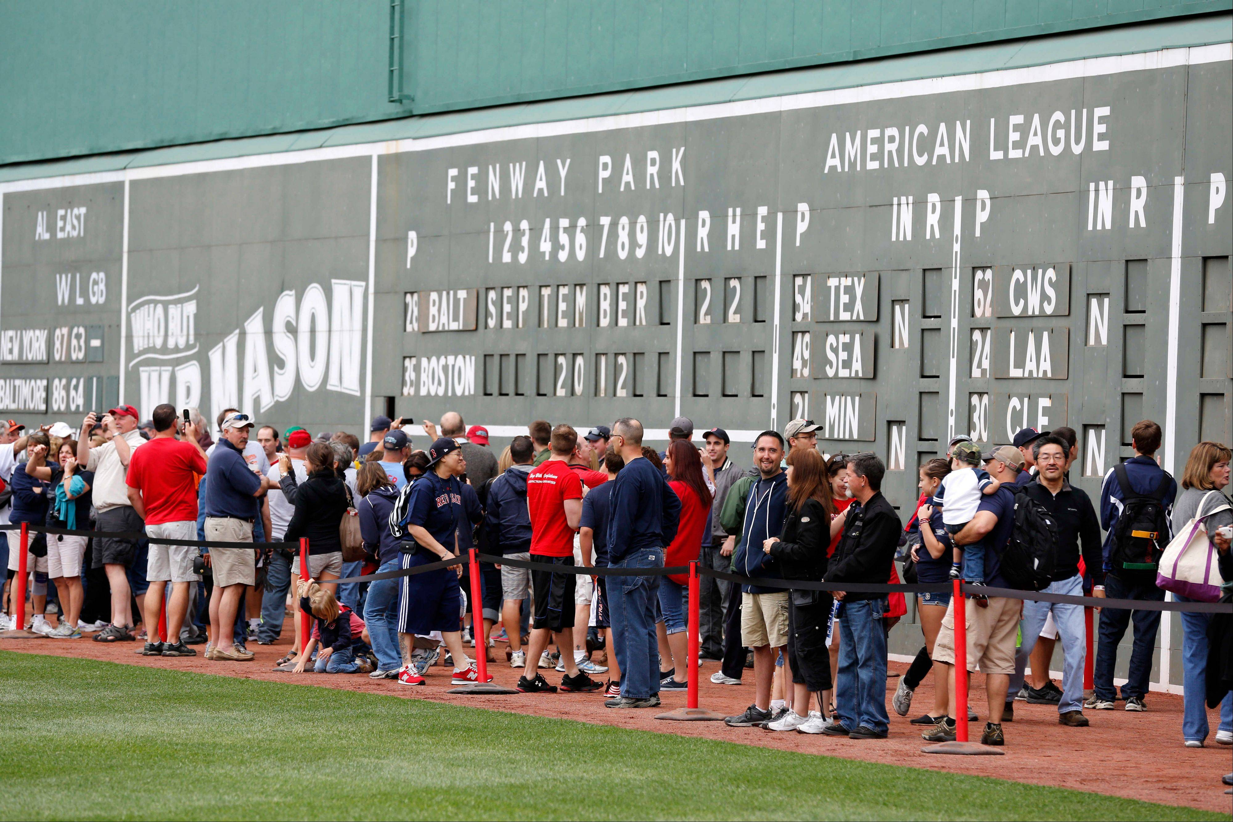 Fans stand in front of the Green Monster scoreboard during On Field Photo Day at Fenway Park in Boston before a baseball game between the Boston Red Sox and the Baltimore Orioles.