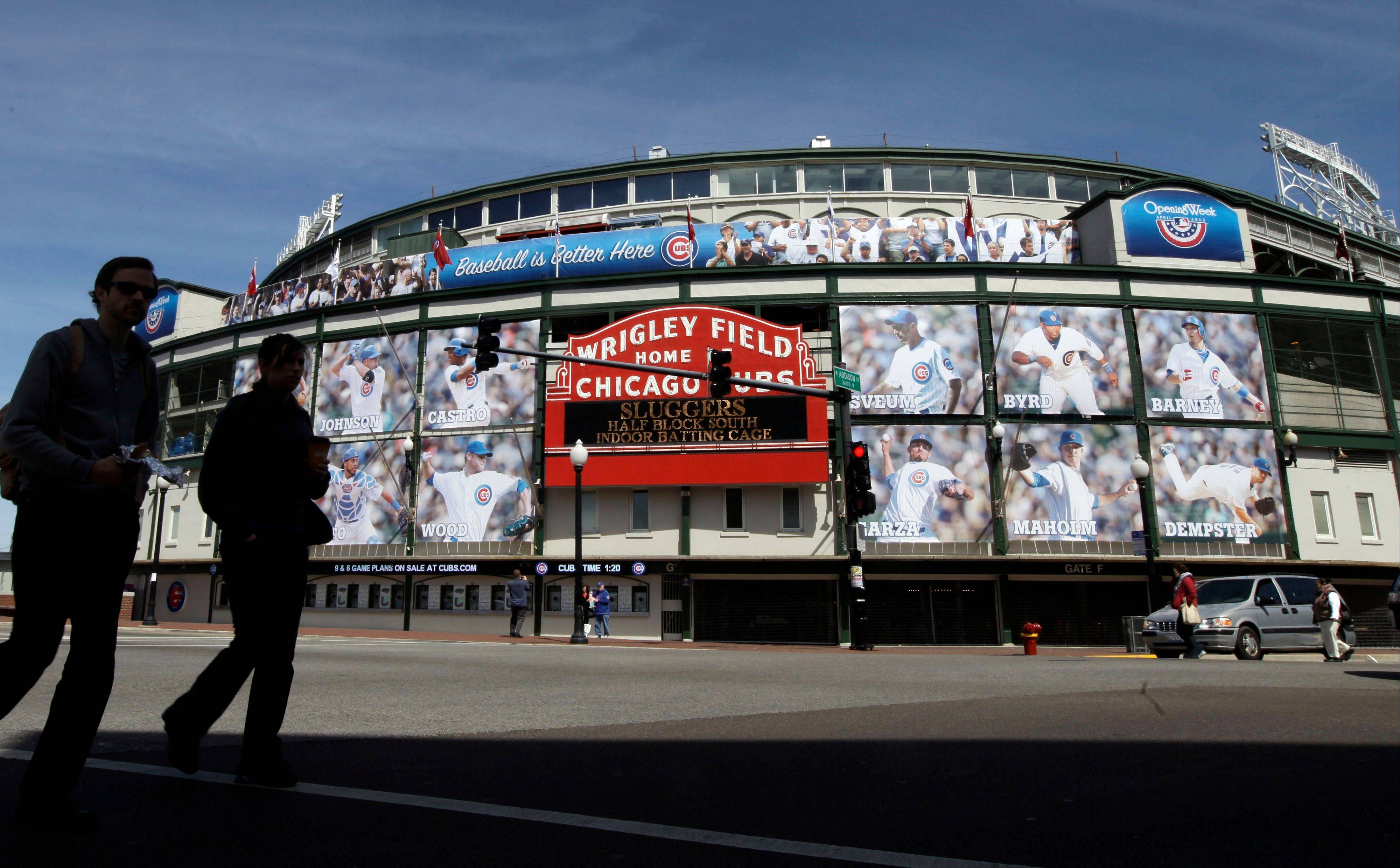 People walk by the marquee at Wrigley Field. All the baseball teams are based in major U.S. cities and many of the stadiums are situated in downtown areas with things to do and savory places to eat when you aren't attending a game.