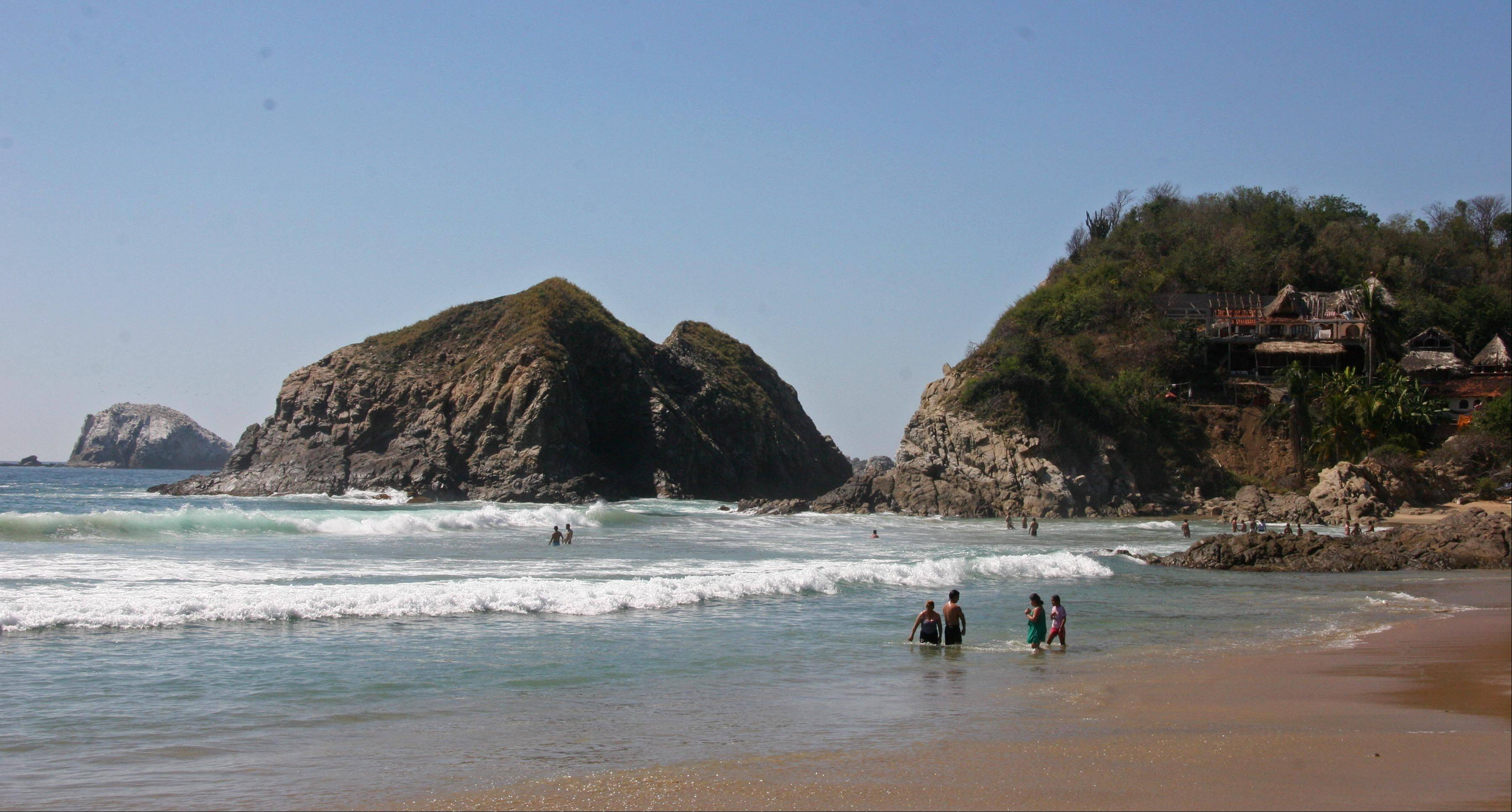 Visitors bath in the surf along the beach in Zipolite.