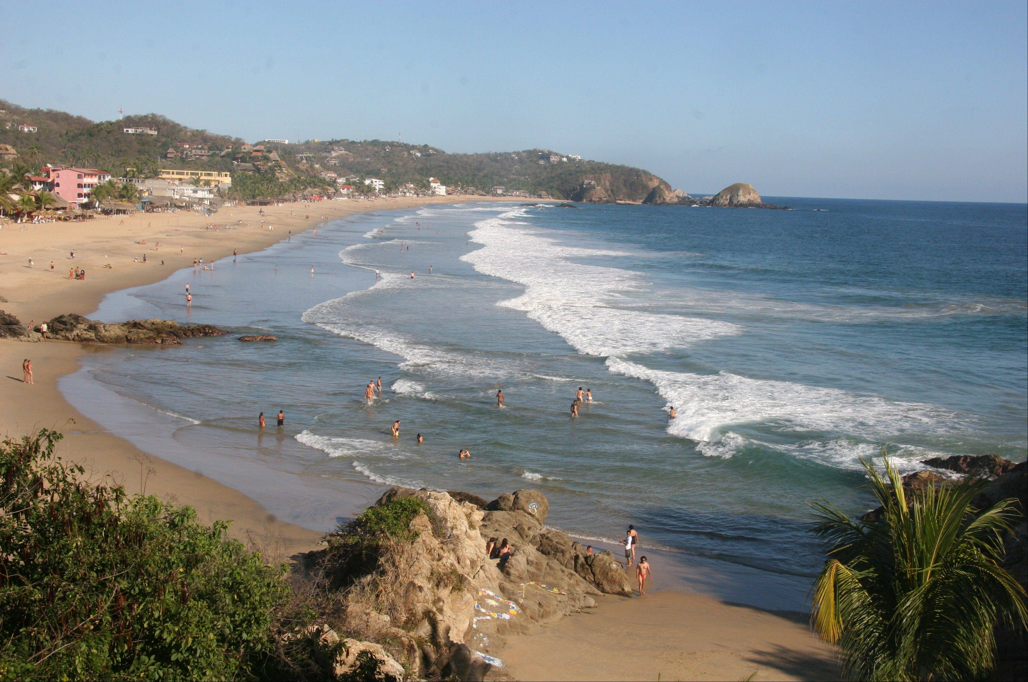 Visitors enjoy the surf along the beach in the sleepy town of Zipolite, Mexico.