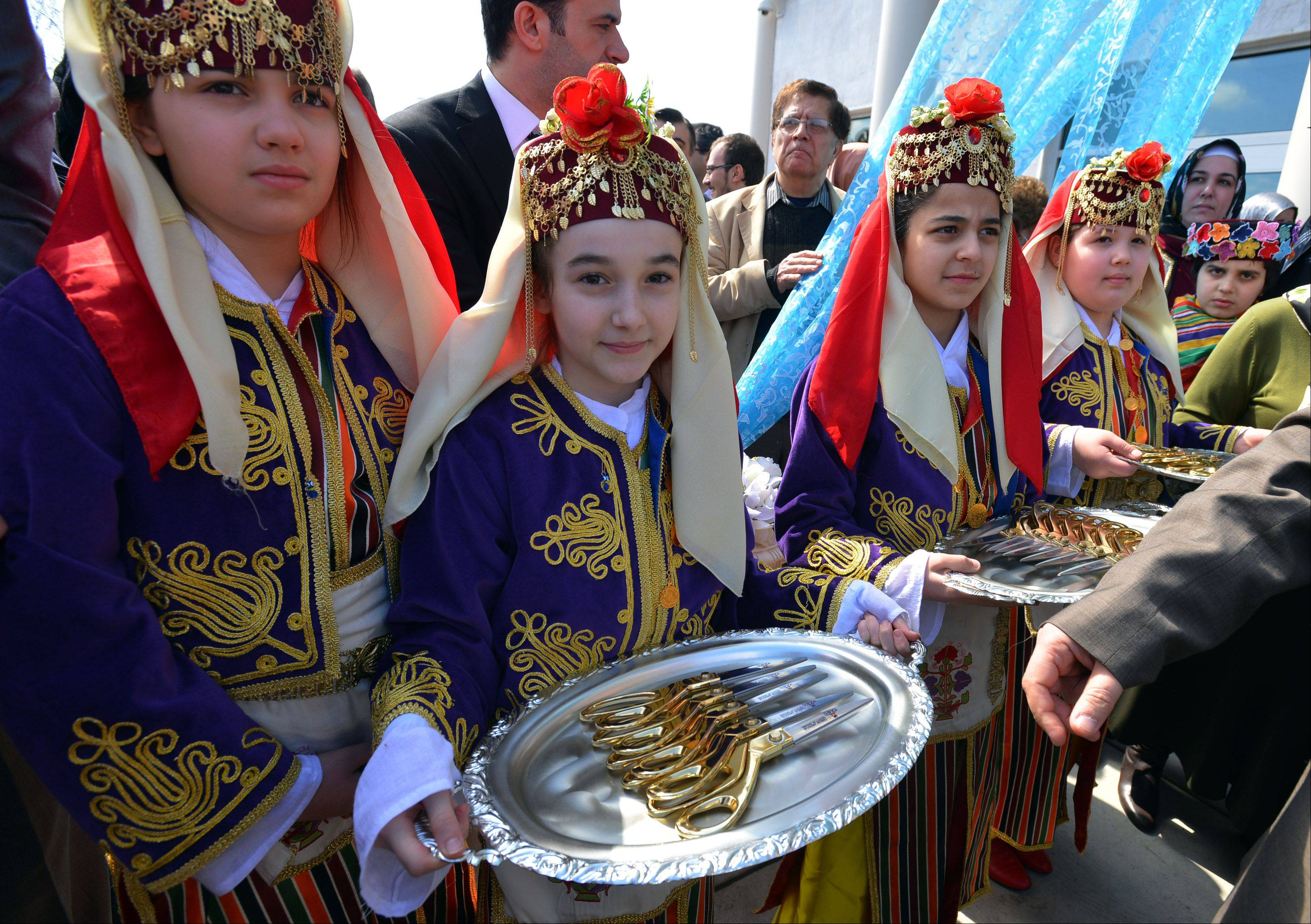 Turkish girls dole out scissors just before the ribbon-cutting ceremony Saturday at the Turkish American Society of Chicago Cultural Center.