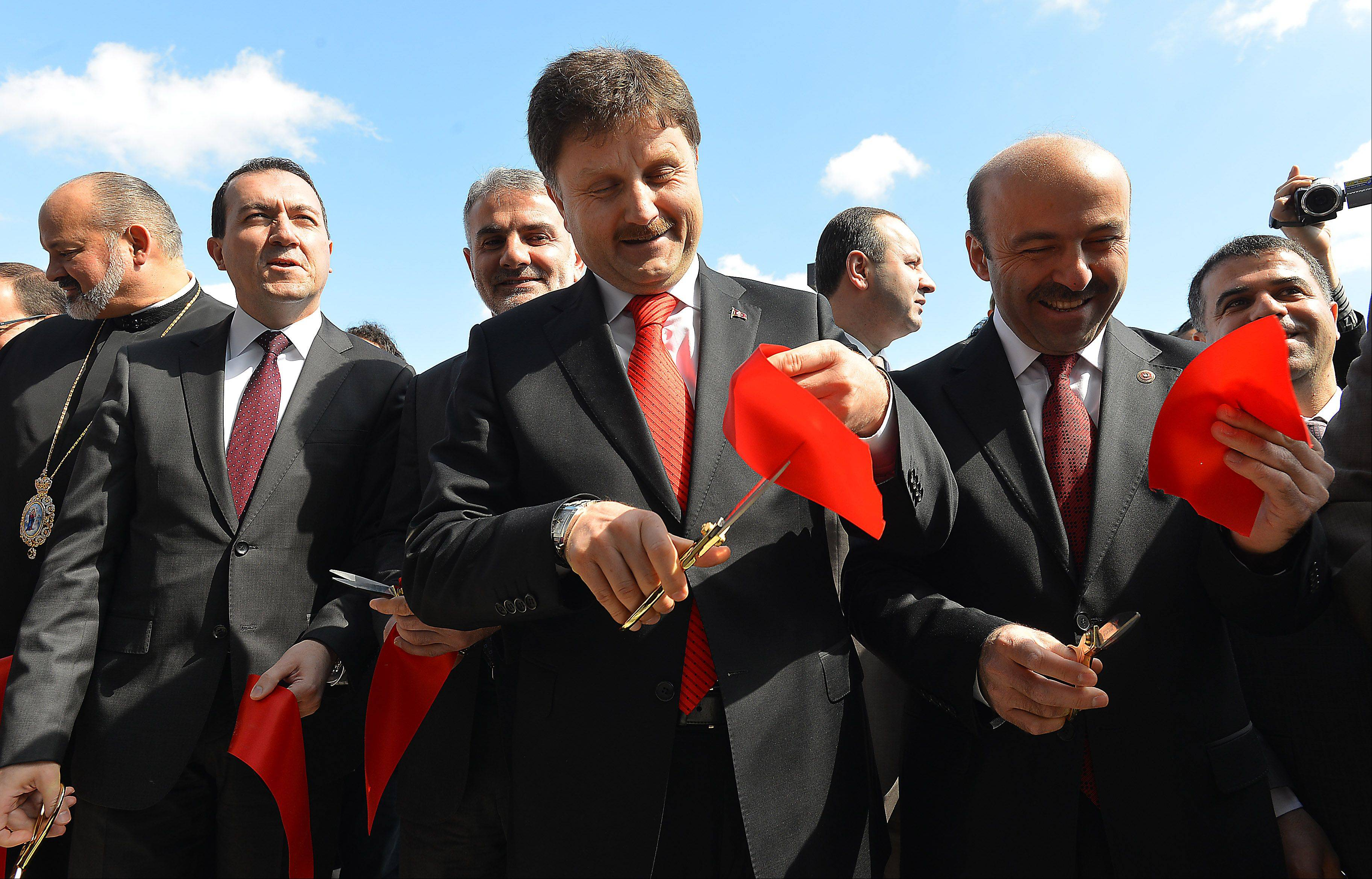 Fahrettin Poyraz, chairperson of the Turkish Parliament, center, takes part in the ribbon-cutting ceremony Saturday to celebrate the Turkish American Society of Chicago Cultural Center's grand opening.