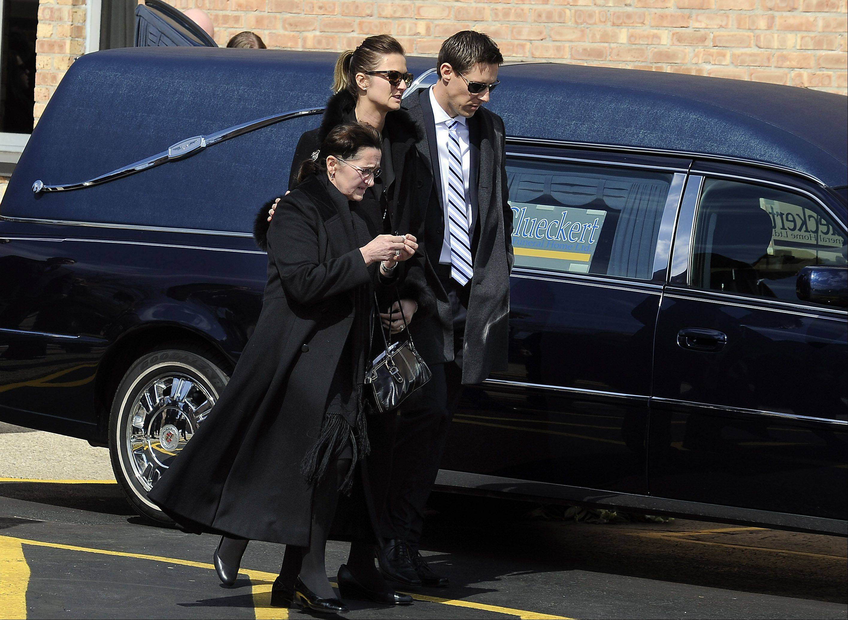 Barbara Komosa, mother of Rob Komosa, and other family members make their way to the cemetery after she attended his funeral service at St. Thomas Becket Church in Mount Prospect on Saturday.