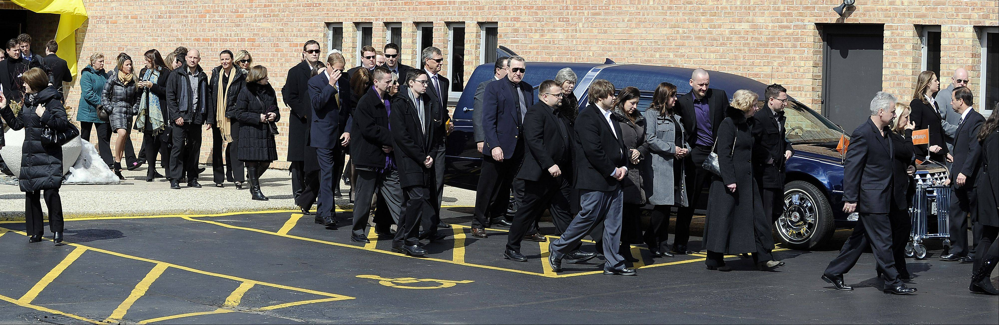 Mourners file past the casket of Rob Komosa after they attended his funeral service at St. Thomas Becket Church in Mount Prospect on Saturday.