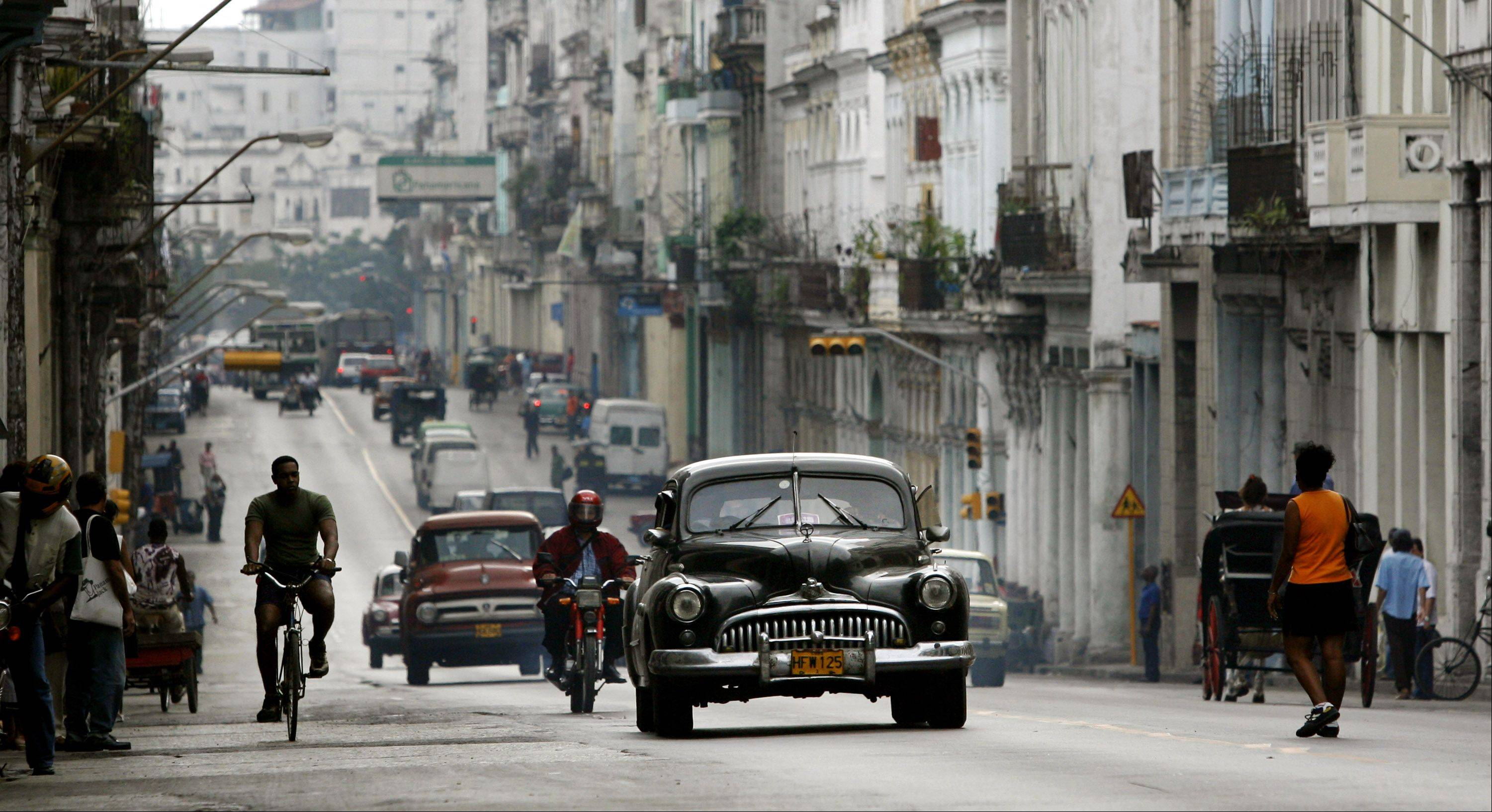 Cubans make their way through an avenue in Havana.