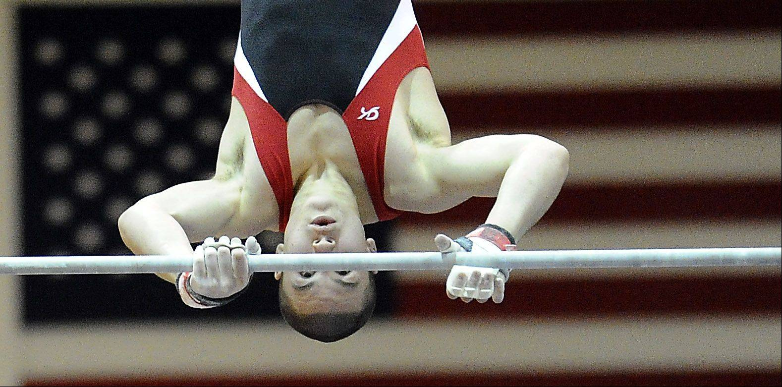Mark Welsh/mwelsh@dailyherald.comGlenbard East's Joey Brauer works the horizontal bar at the Vic Avigliano Mustang Gymnastics Invitational at Rolling Meadows High School on Saturday.