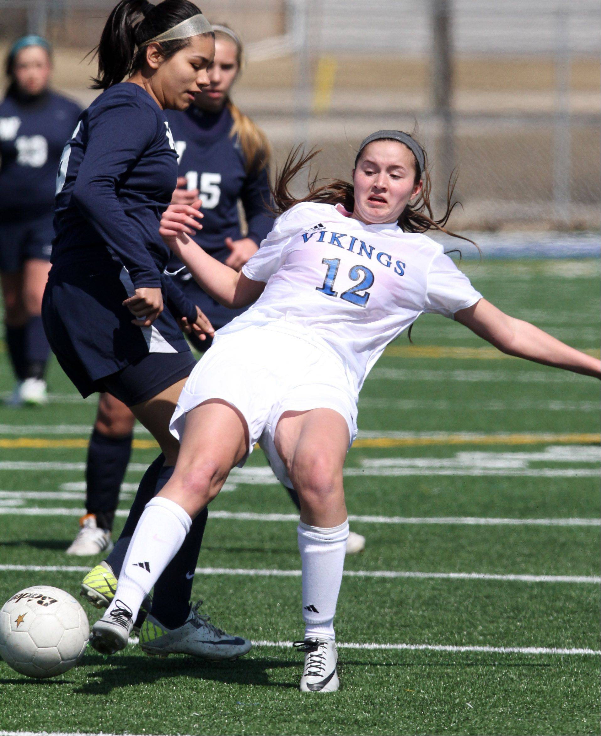 Geneva's Maggie Bodine kicks the ball as she is slipping against West Aurora defender at Geneva on Saturday, March 23, 2013.