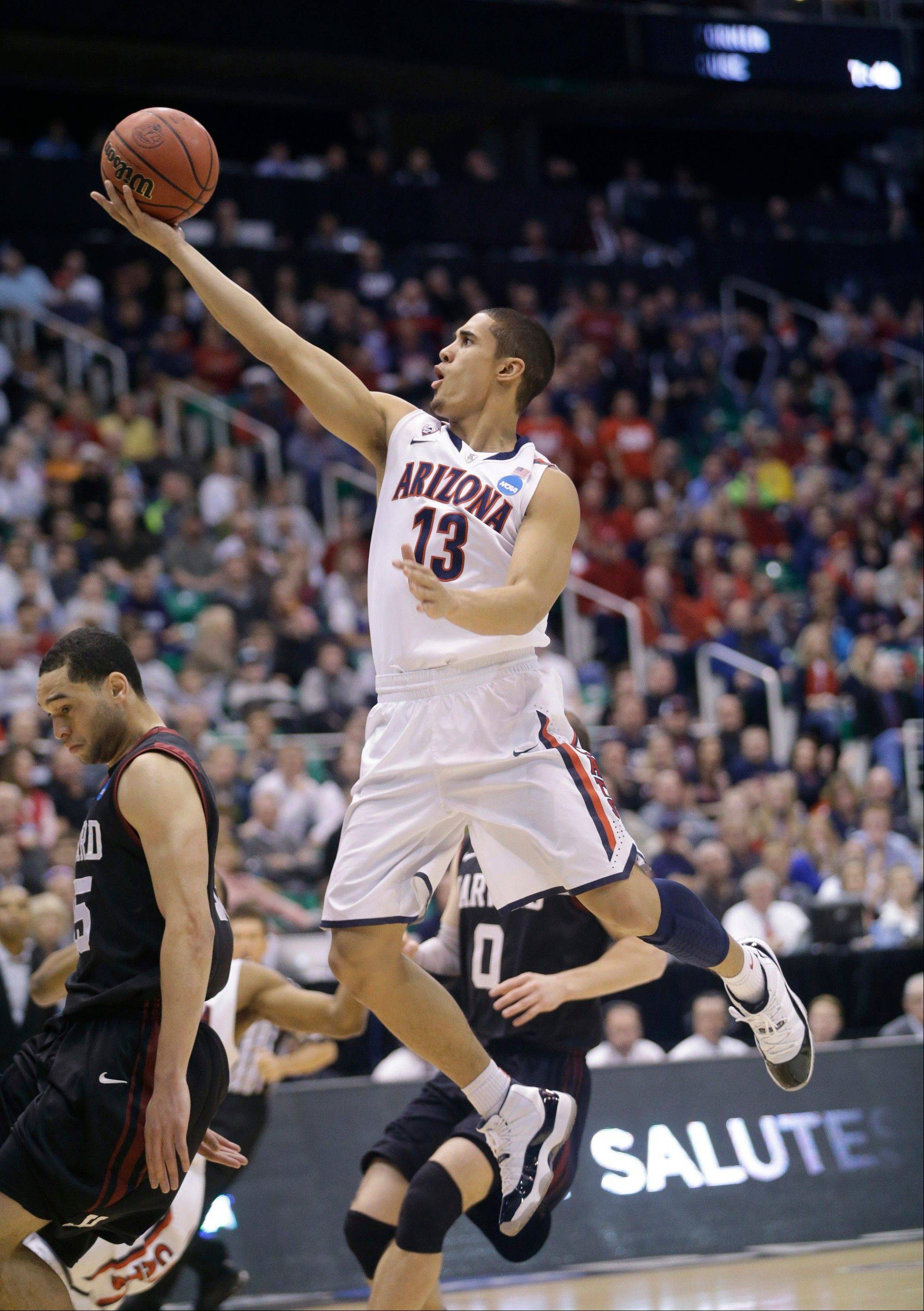 Arizona's Nick Johnson (13) lays the ball up next to Harvard's Christian Webster in the first half during a third-round game in the NCAA men's college basketball tournament in Salt Lake City, Saturday, March 23, 2013.