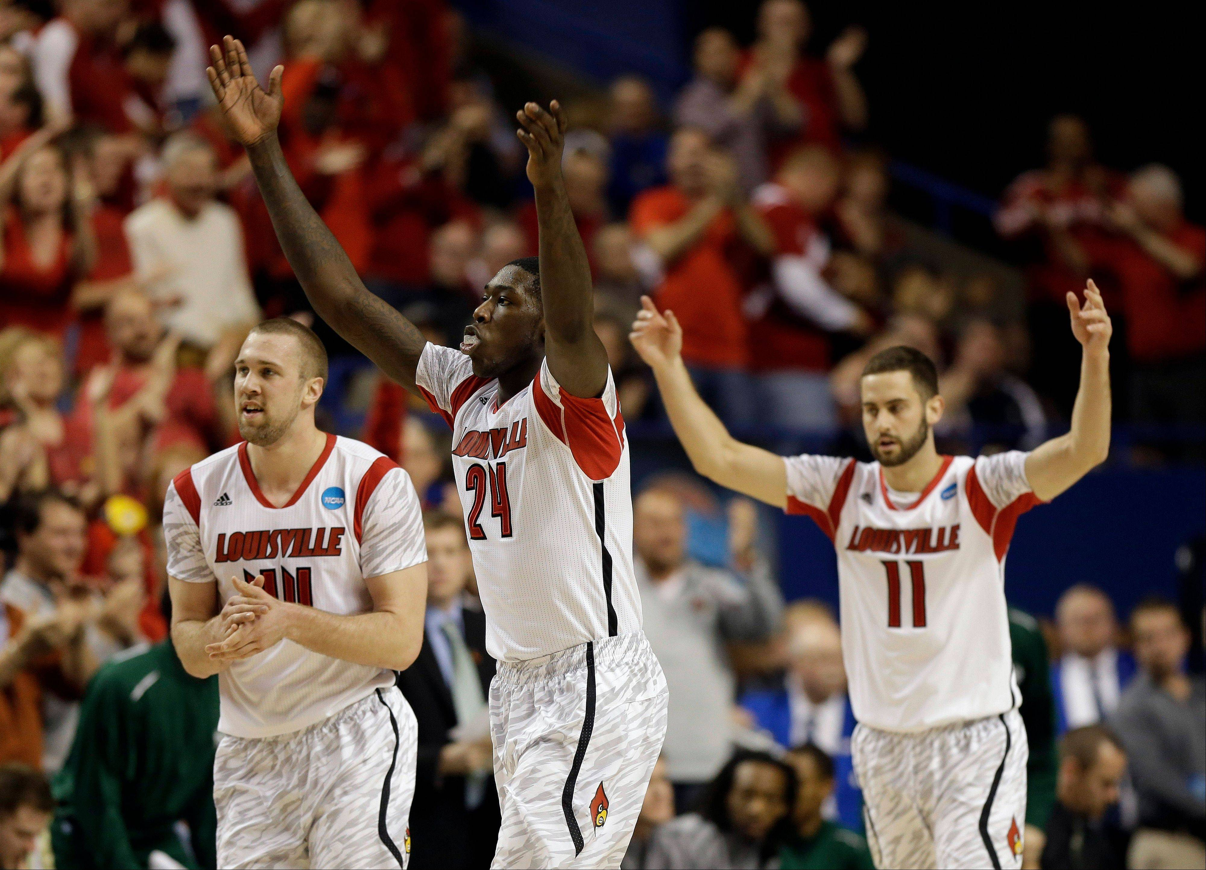 From left to right, Louisville's Stephan Van Treese, Montrezl Harrell and Luke Hancock react after a basket in the first half of a third-round NCAA college basketball tournament game against Colorado State, Saturday, March 23, 2013, in Lexington, Ky.