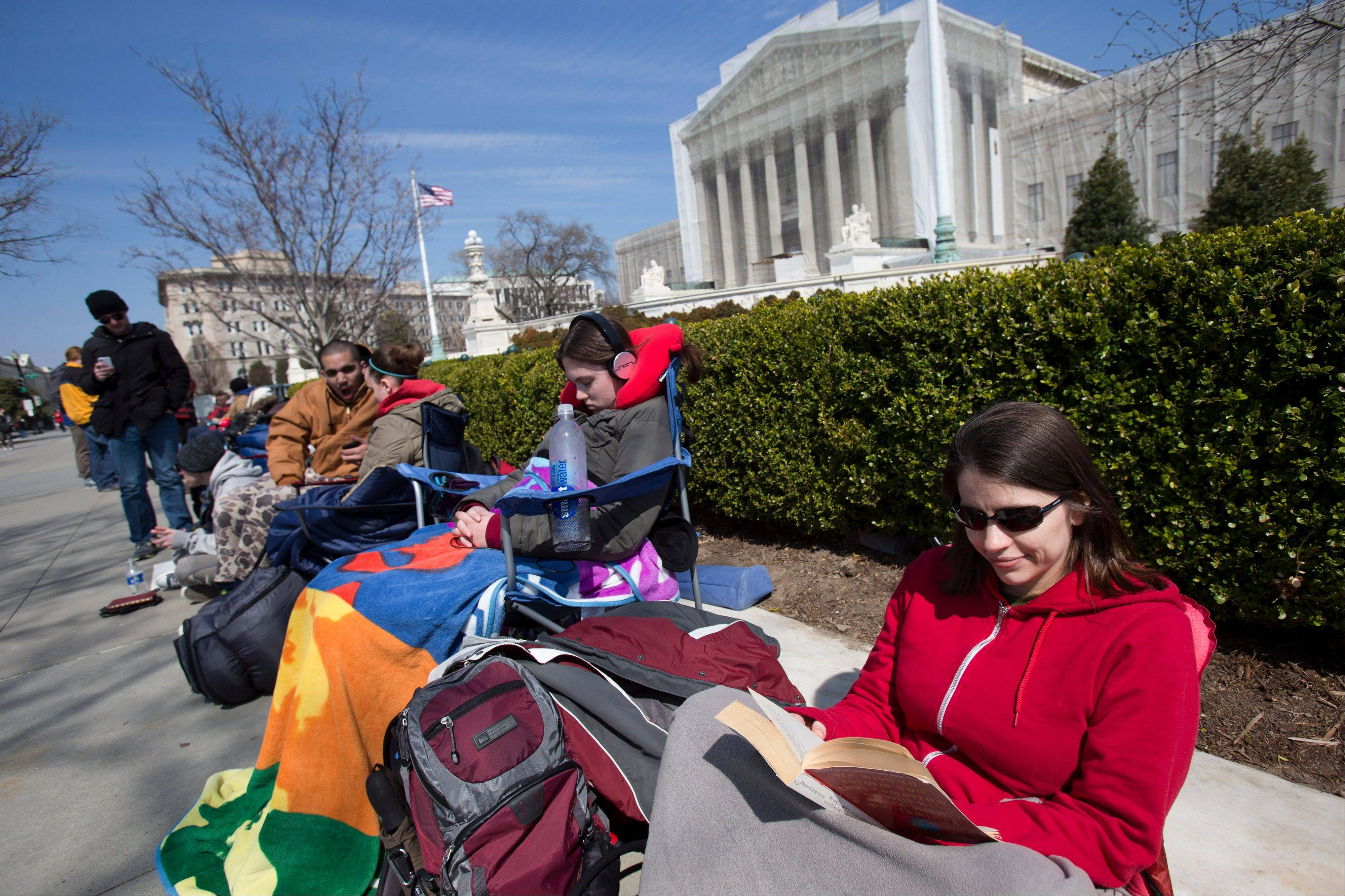 Jessica Skrebes of Washington reads Saturday while waiting in line with others outside of the U.S. Supreme Court in Washington in anticipation of Tuesday's Supreme Court hearing on California's Proposition 8 ban on same-sex marriage, and Wednesday's Supreme Court hearing on the federal Defense of Marriage Act.