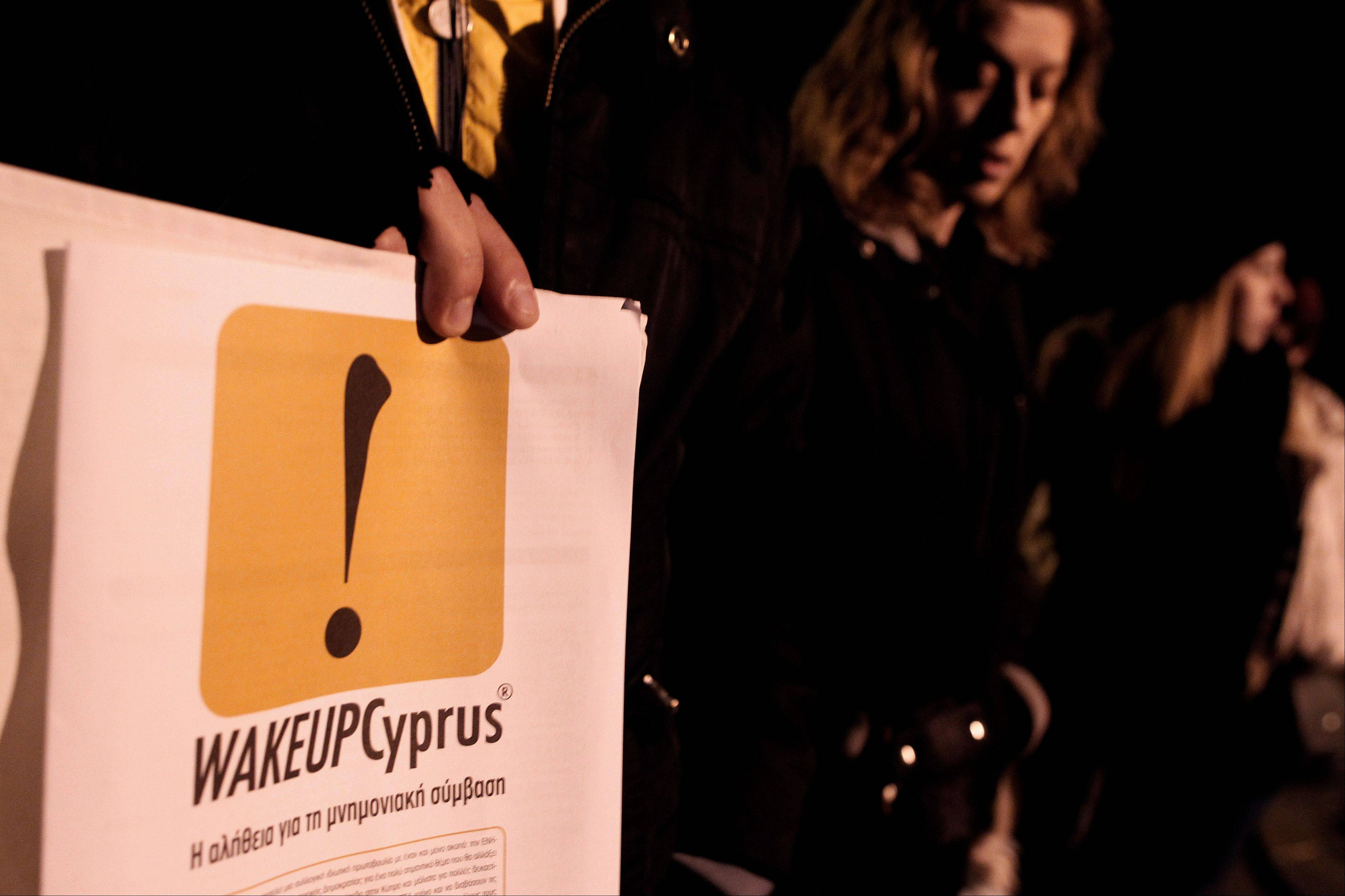 Protesters take part in an anti-bailout rally outside the Cyprus Presidential palace in Nicosia Sunday. Cyprus secured a package of rescue loans in tense, last-ditch negotiations early Monday, two EU diplomats said, saving the country from a banking system collapse and bankruptcy.