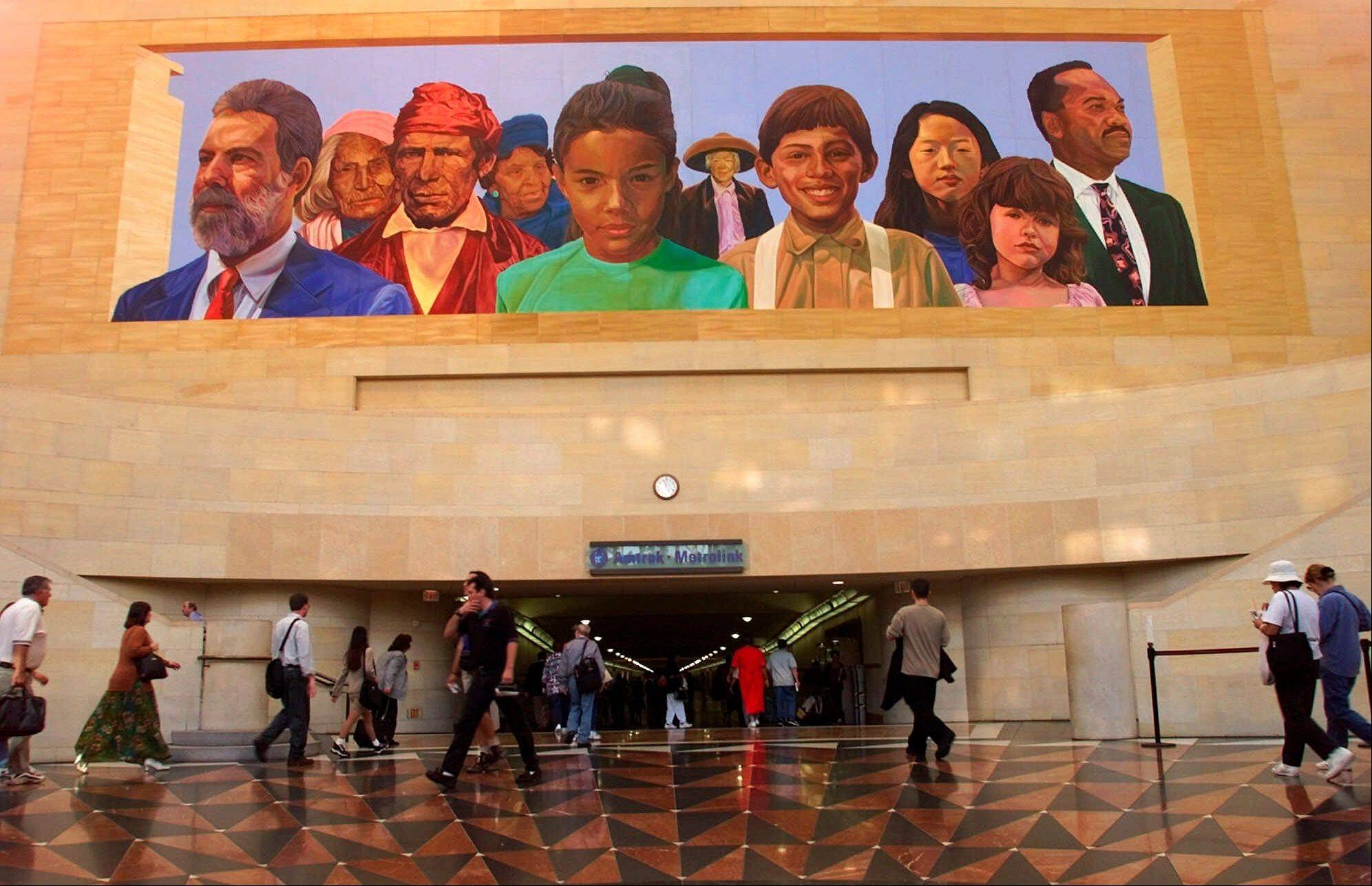 "Commuters walk into a tunnel at Los Angeles's Amtrack-Metrolink Union Station under the mural ""City of Dreams/River of History"" by artist Richard Wyatt, showing the diversity of California's population."