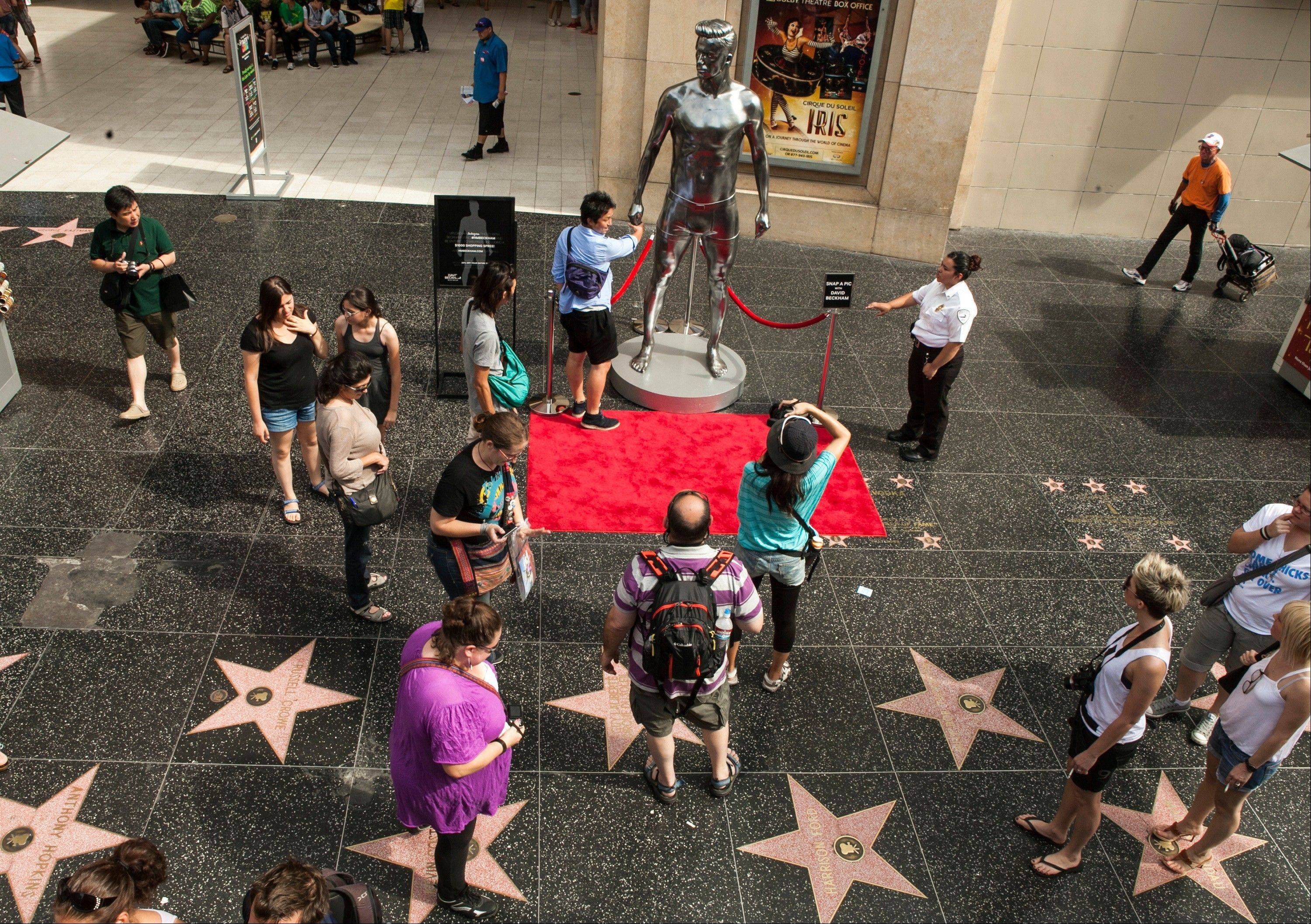 Tourists take photos with a 10-foot statue created and modeled after English soccer star David Beckham displayed in the Hollywood section of Los Angeles. The intersection of Hollywood and Highland is the crossroads for the Hollywood Walk of Fame.