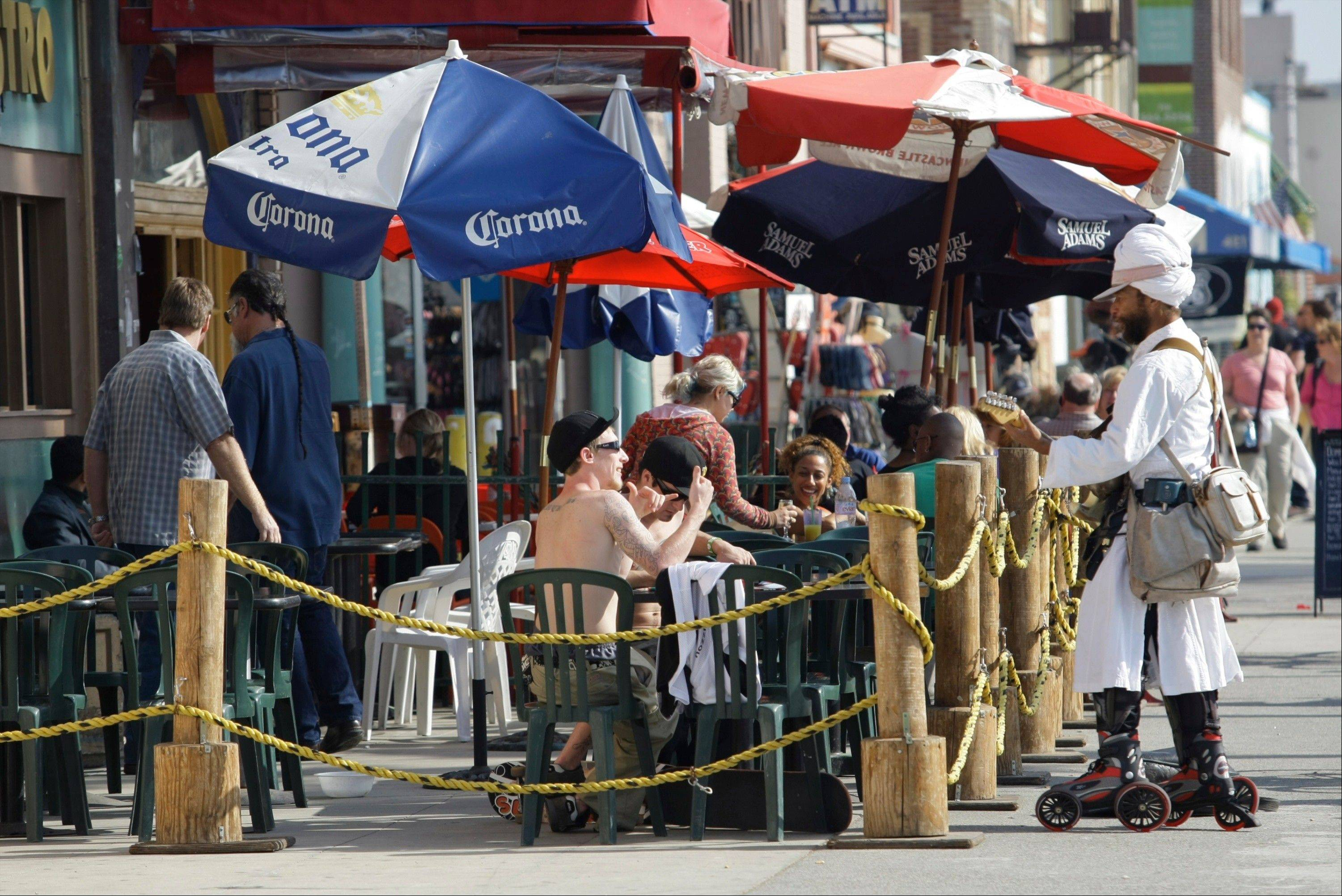 Musician Harry Perry, twangs an electric guitar as he Rollerblade up and down the Venice Beach boardwalk garbed in a turban and tunic in Los Angeles. Venice Beach, arguably the best free people-watching venue anywhere west of New York's Times Square and with the added bonus that it never gets really cold here.